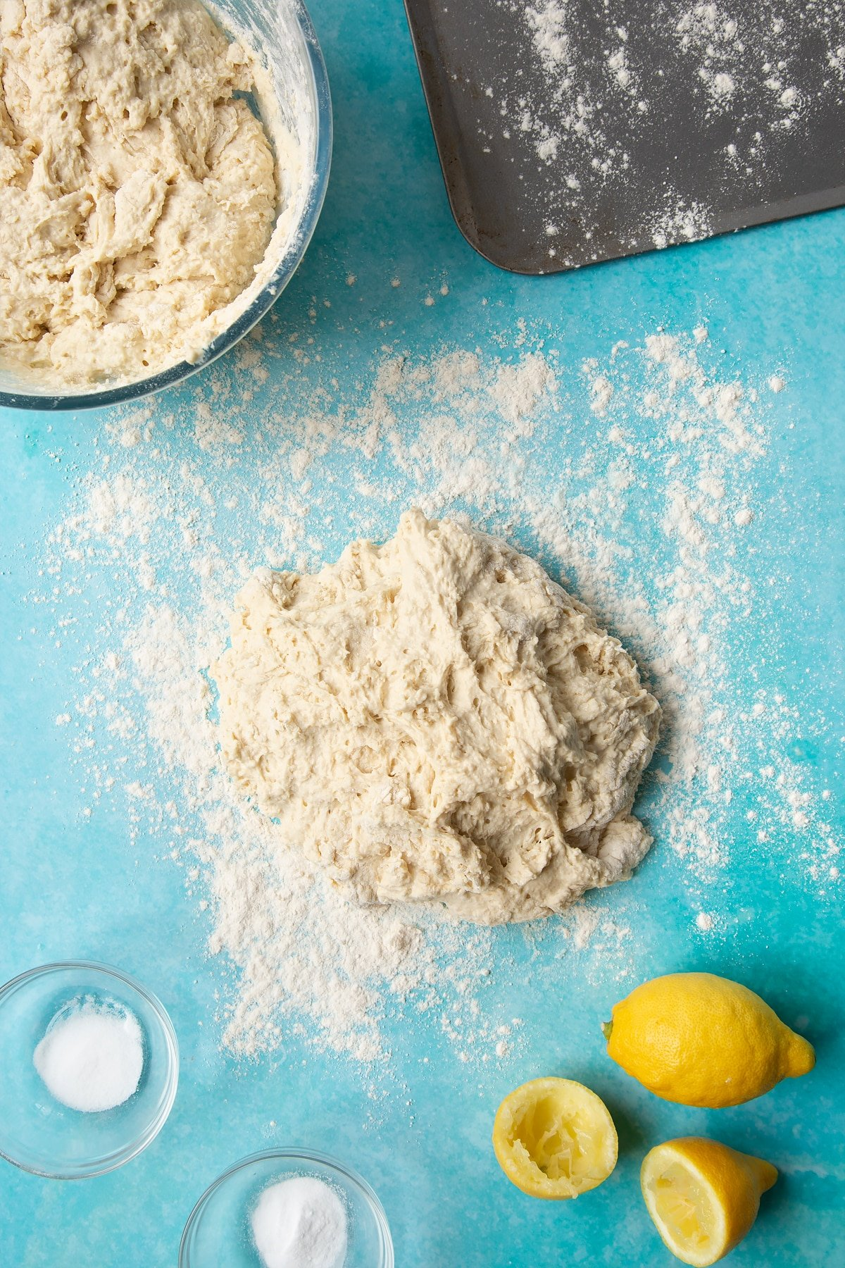 A wet dough on a floured surface surrounded by ingredients to make vegan soda bread.