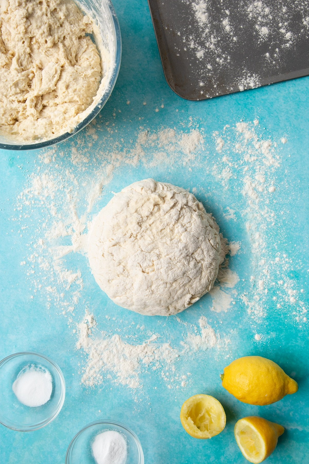 A shaped soda bread dough on a floured surface surrounded by ingredients to make vegan soda bread.