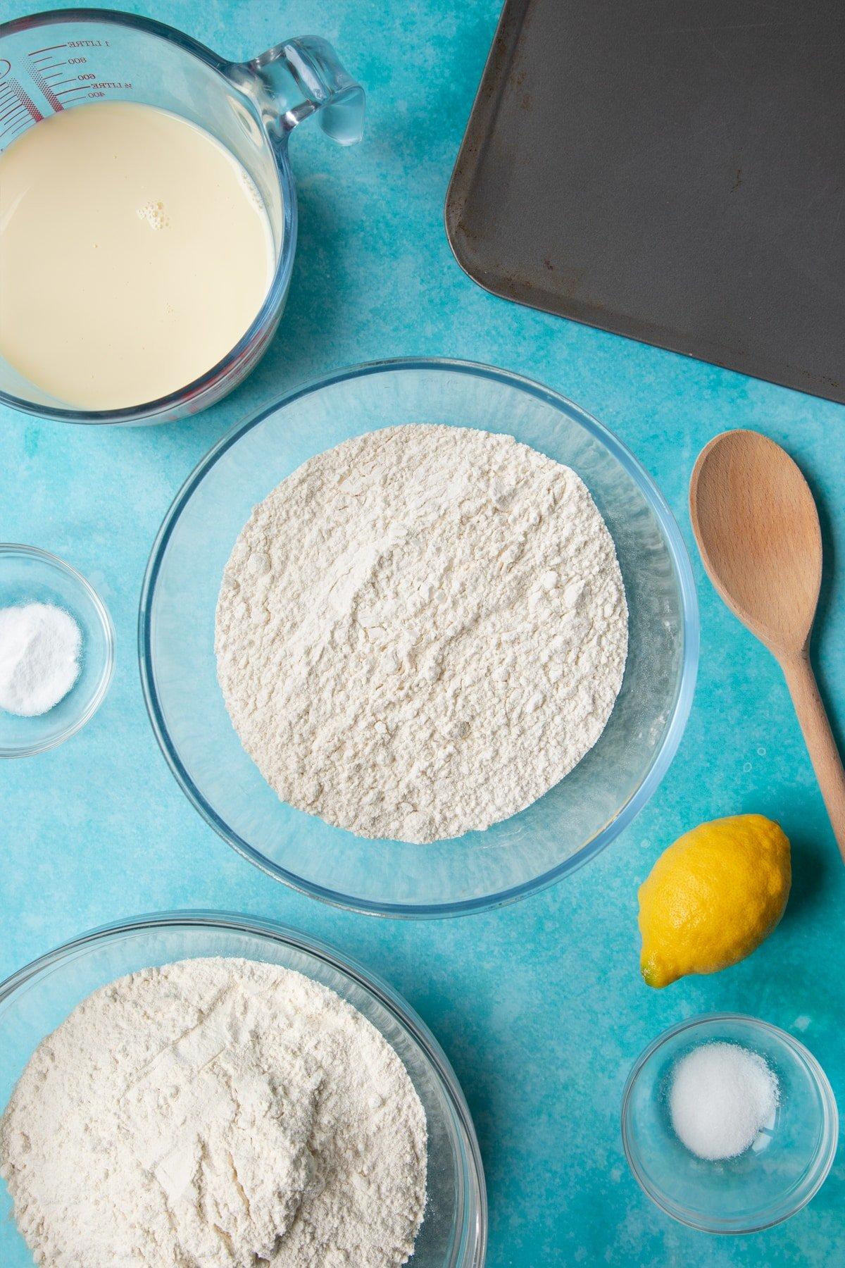 A bowl containing plain flour. Ingredients to make vegan soda bread surround the bowl.