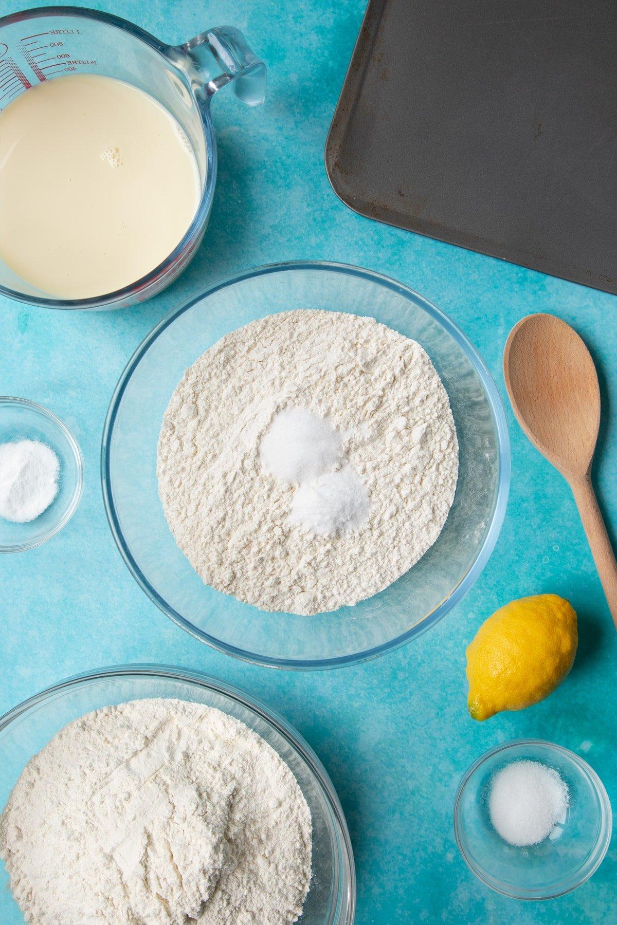 A bowl containing plain flour, salt and bicarbonate of soda. Ingredients to make vegan soda bread surround the bowl.