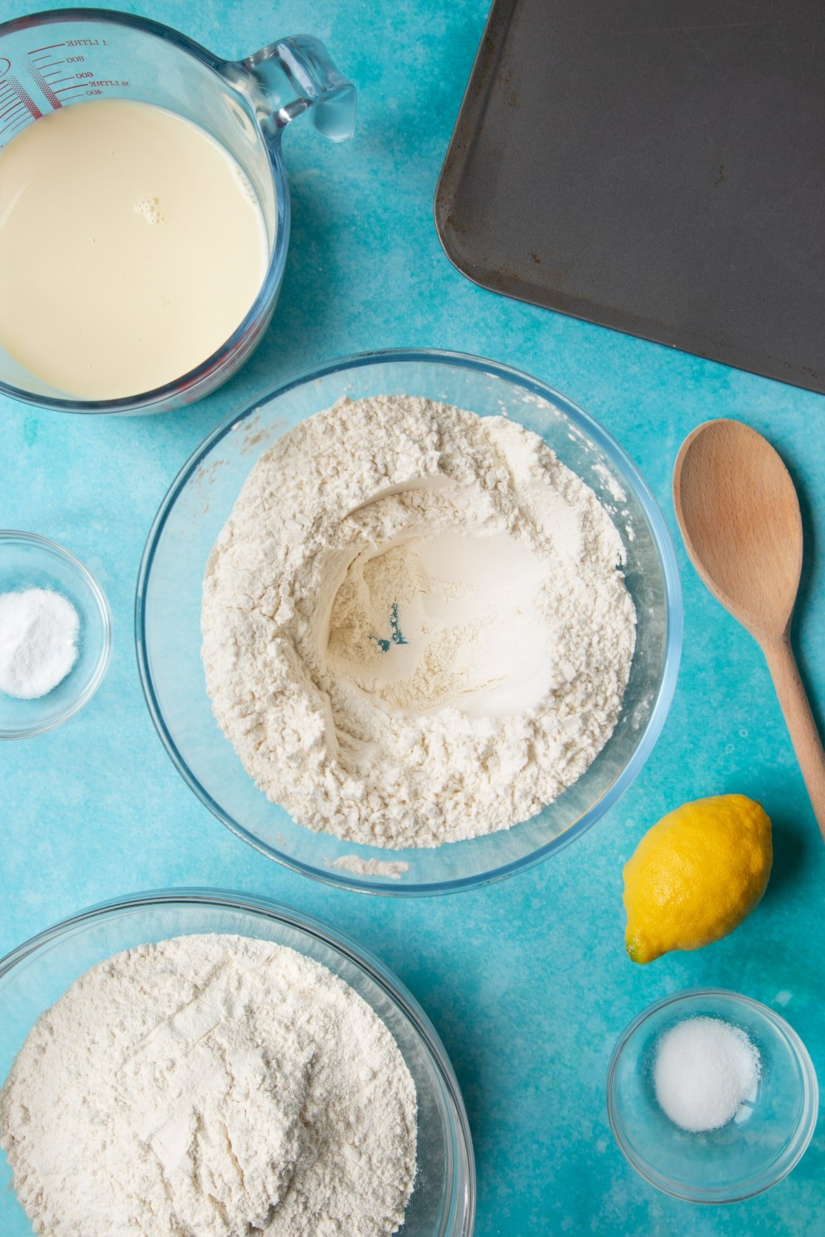 A bowl containing plain flour, salt and bicarbonate of soda, mixed with a well in the centre. Ingredients to make vegan soda bread surround the bowl.