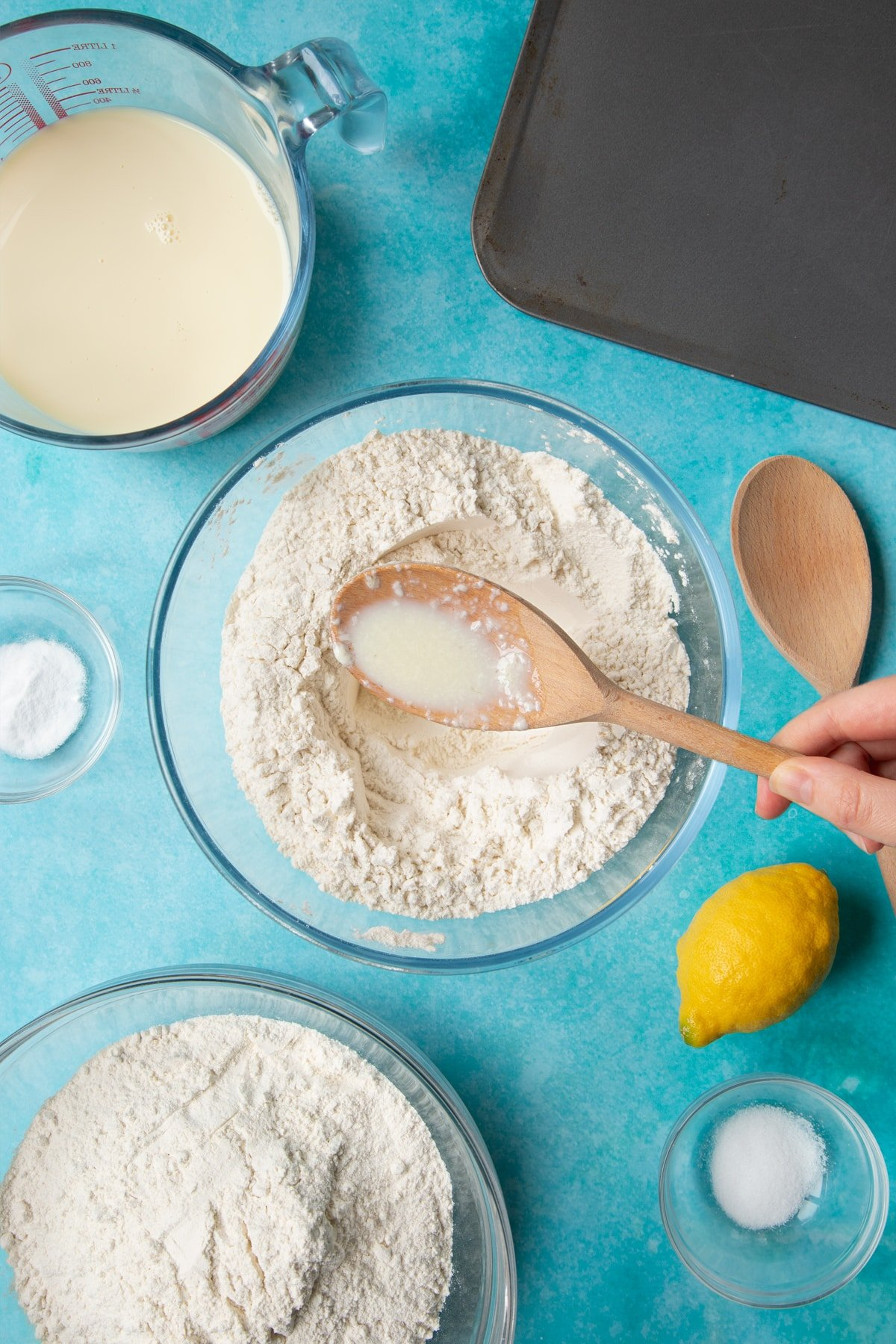 A bowl containing plain flour, salt and bicarbonate of soda. A hand holds a spoon with plant milk on it. Ingredients to make vegan soda bread surround the bowl.