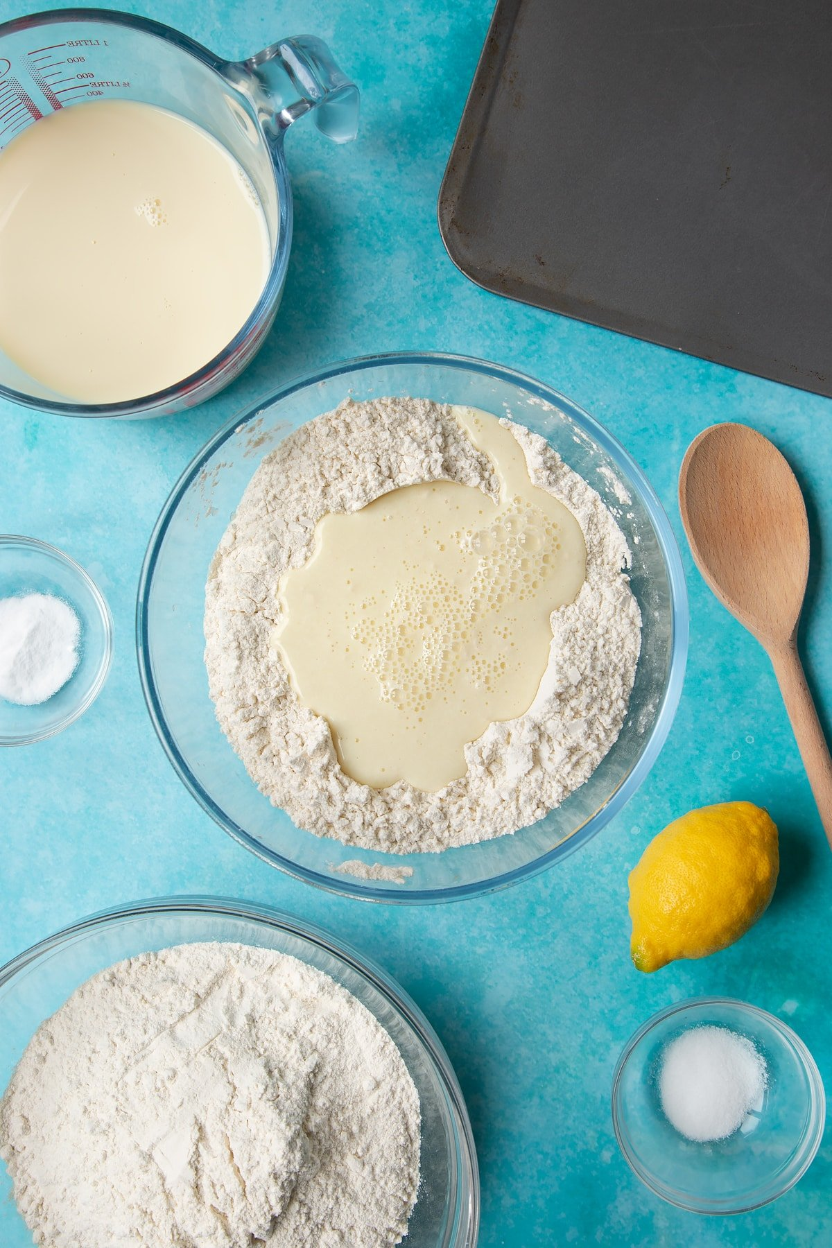 A bowl containing plain flour, salt and bicarbonate of soda, mixed with a well in the centre filled with plant milk. Ingredients to make vegan soda bread surround the bowl.