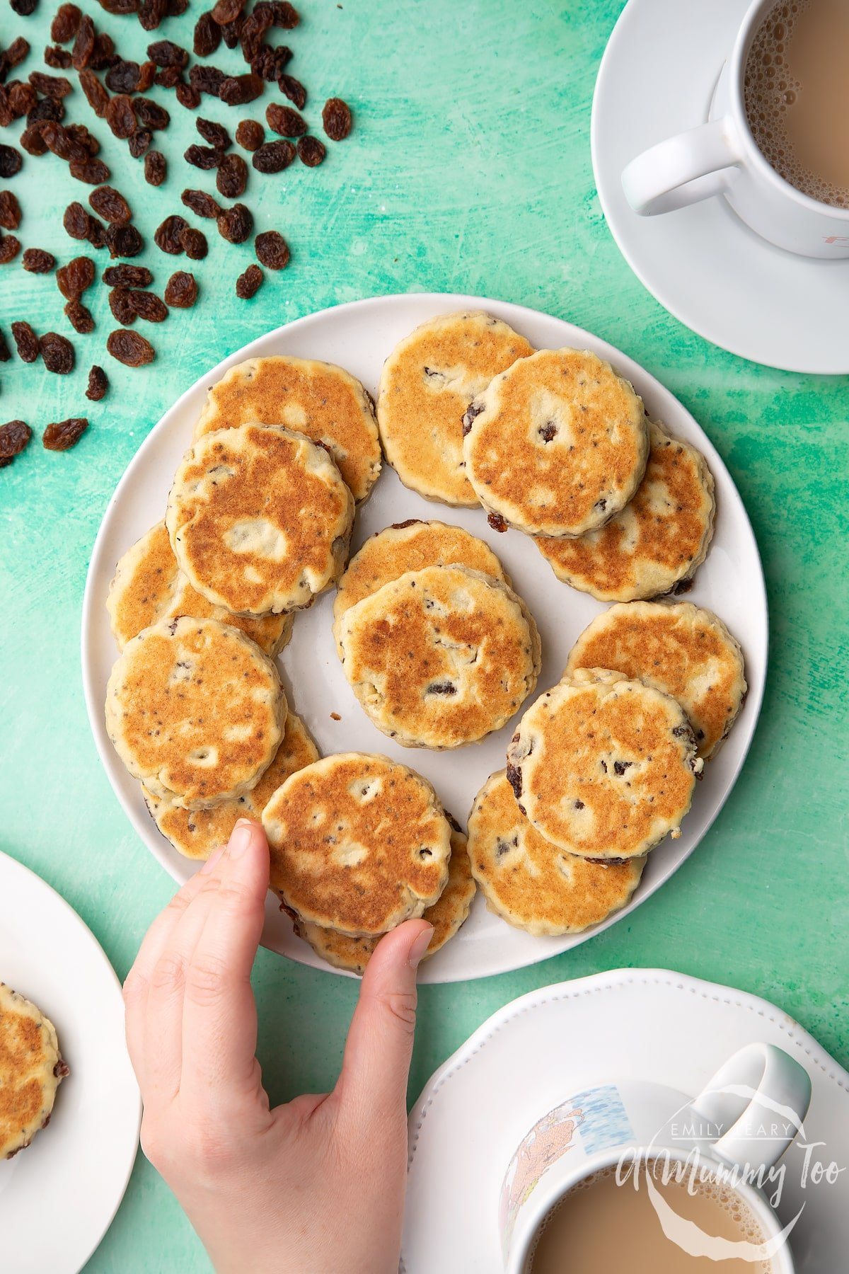 Vegan Welsh cakes arranged on a white plate. Surrounding the plate are cups of tea. A hand reaches in to take a Welsh cake.