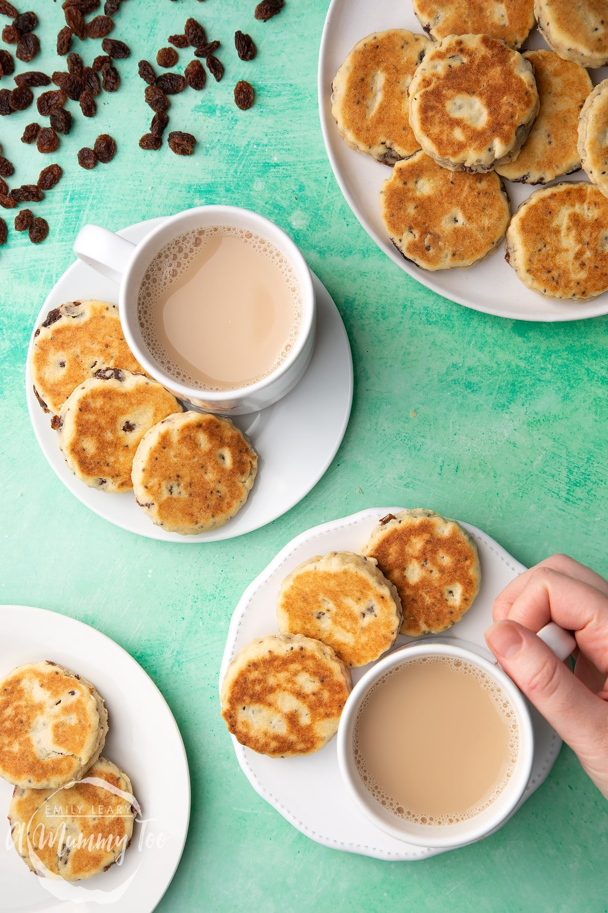 Vegan Welsh cakes arranged on a white plates with cups of tea. A hand reaches in to take a cup.