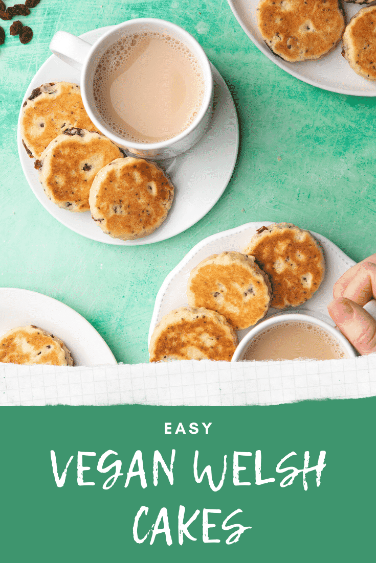 Vegan Welsh cakes arranged on small white plates with cups of tea. Caption reads: Easy vegan Welsh cakes.