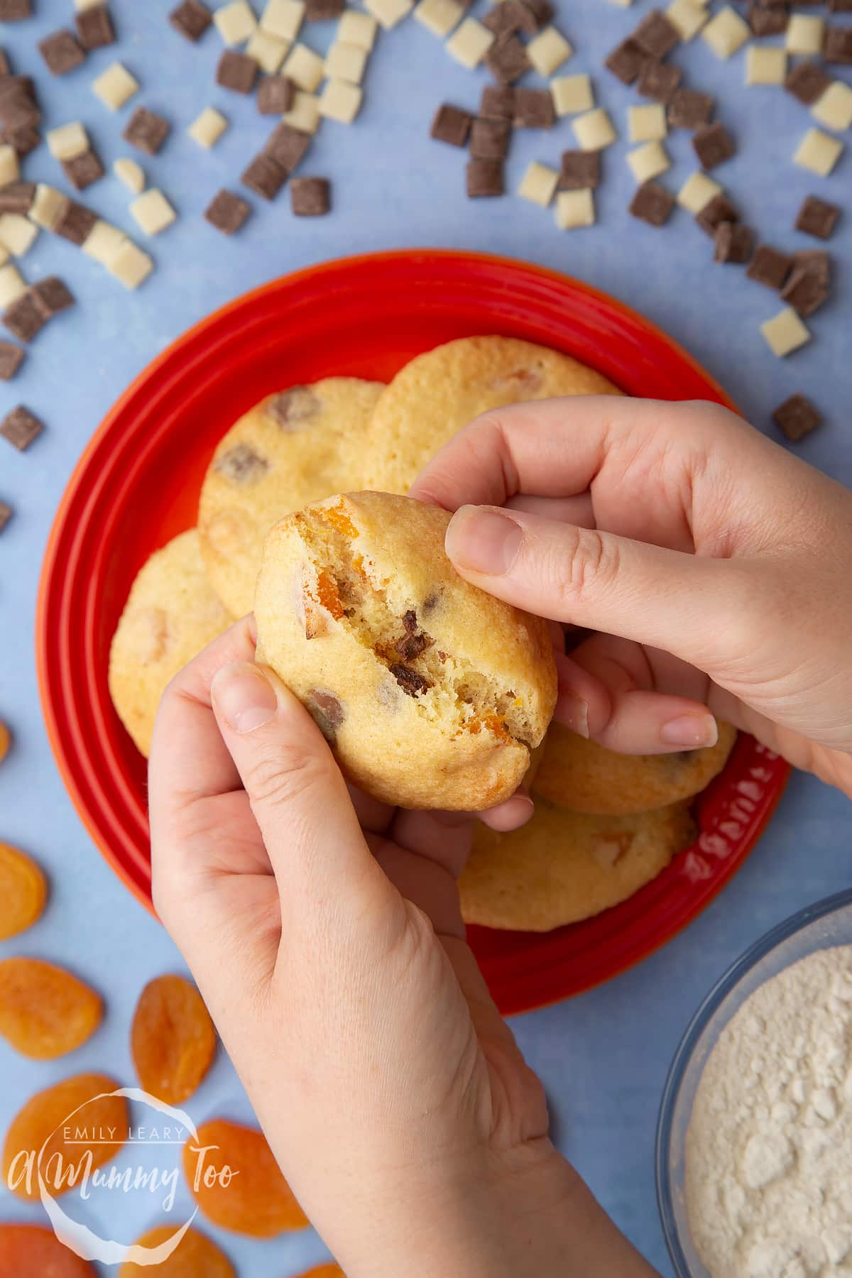 Apricot chocolate chip cookies stacked on an orange plate. Hands break one open.