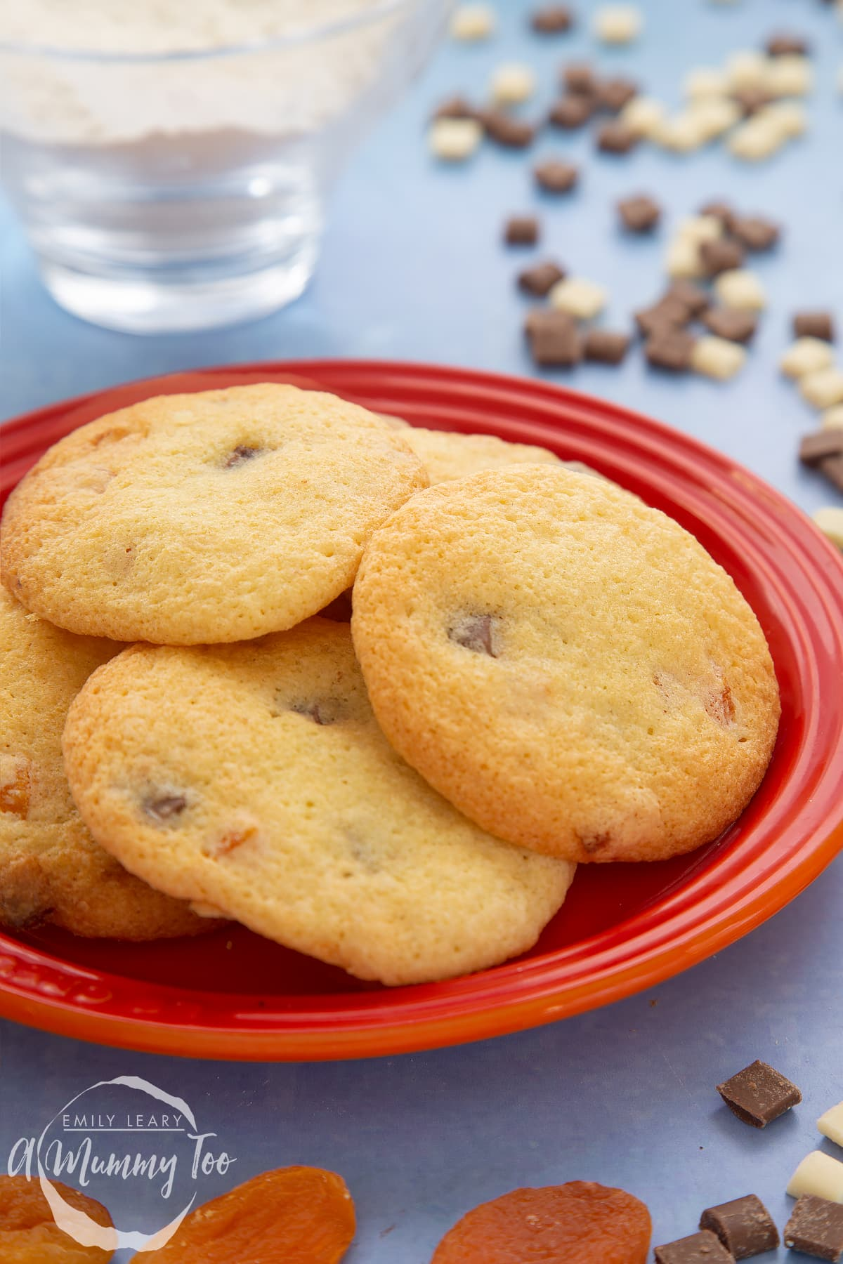 Apricot chocolate chip cookies on a small orange plate. Chocolate chips and dried apricots are scattered around.