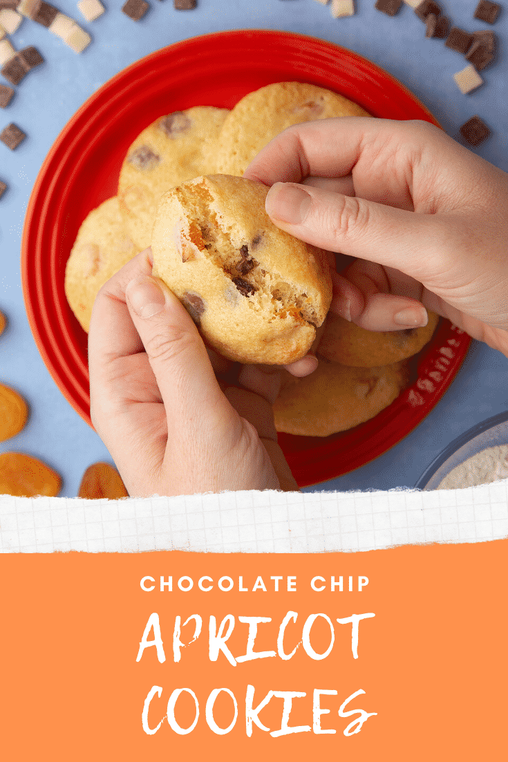 Apricot chocolate chip cookies stacked on a small orange plate. Hands break a cookie in half. Caption reads: apricot chocolate chips cookies