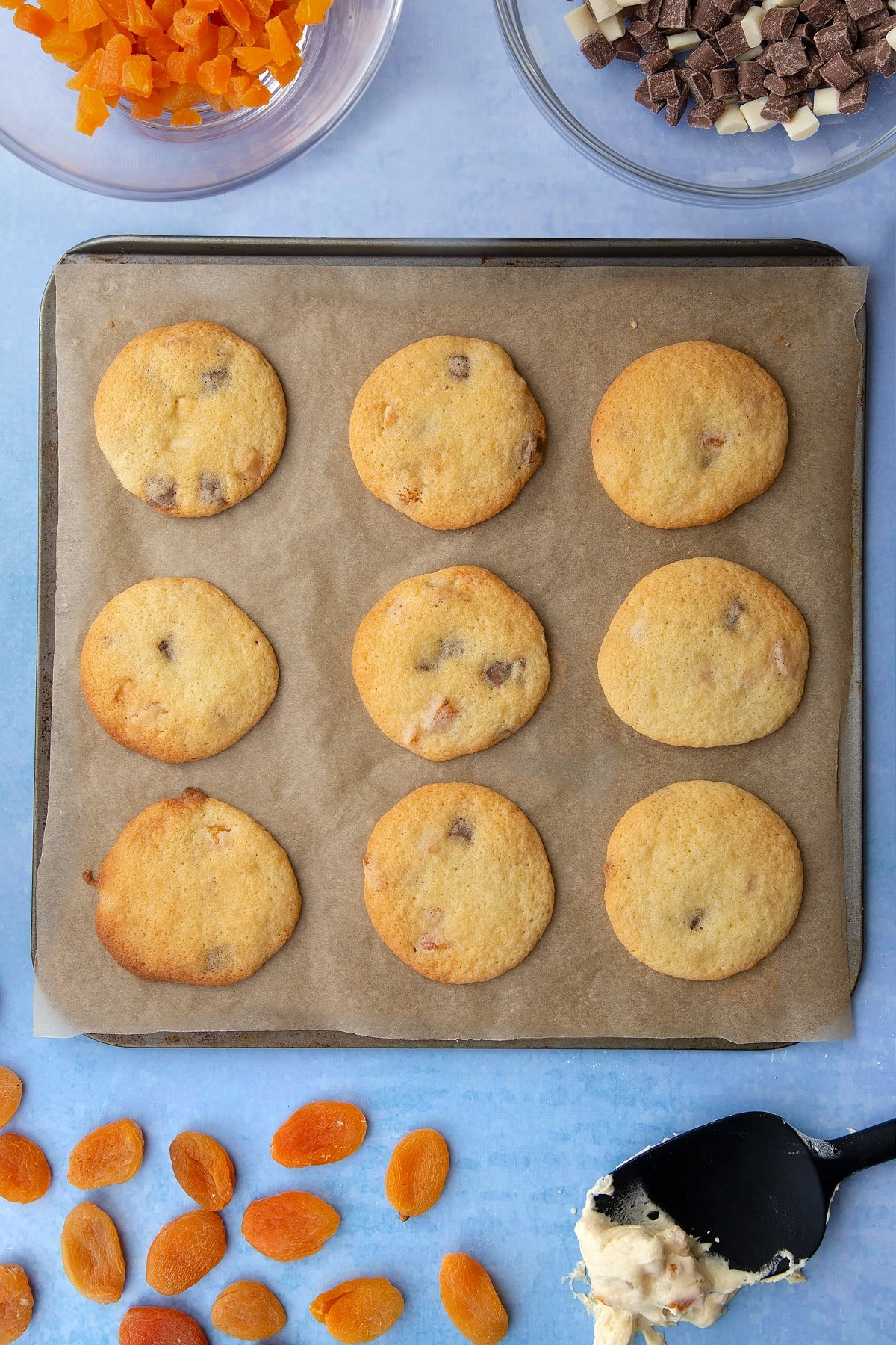 Freshly baked chocolate and apricot cookies on a tray lined with baking paper. Ingredients to make apricot chocolate chip cookies surround the tray.