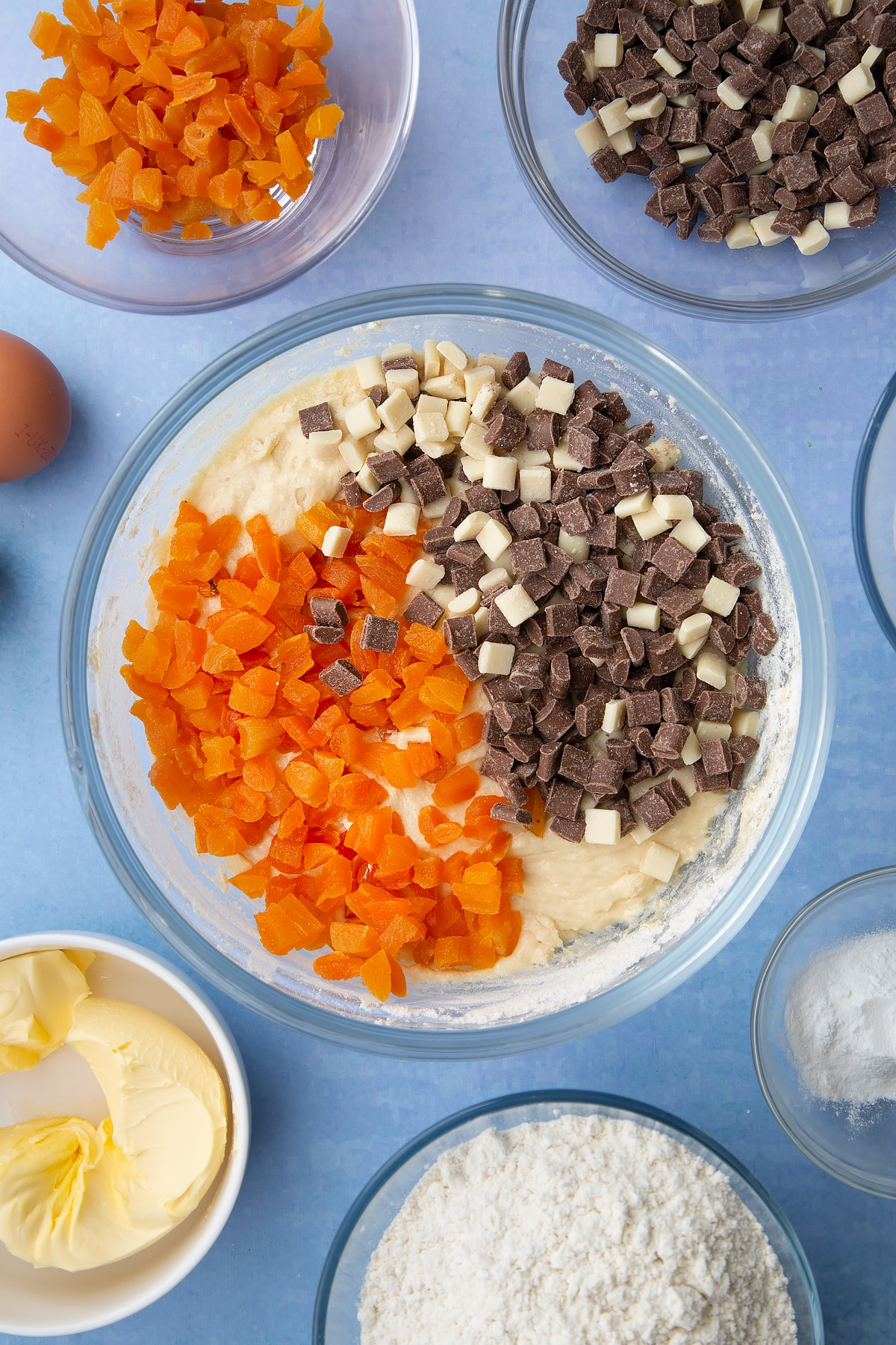 Cookie dough in a glass mixing bowl with chopped dried apricots and chocolate chips on top. Ingredients to make apricot chocolate chip cookies surround the bowl.