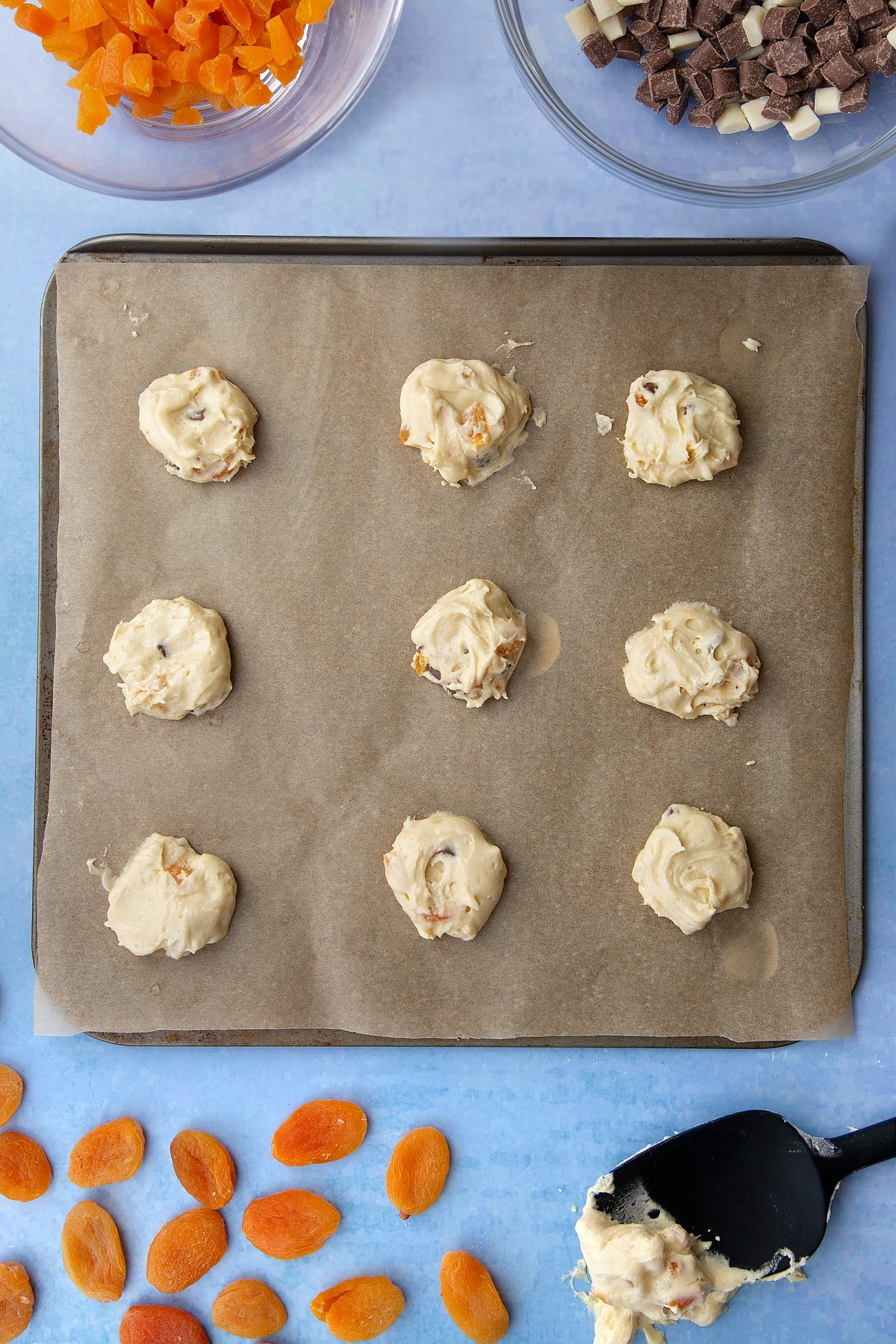 Chocolate and apricot cookie dough blobs on a tray lined with baking paper. Ingredients to make apricot chocolate chip cookies surround the tray.