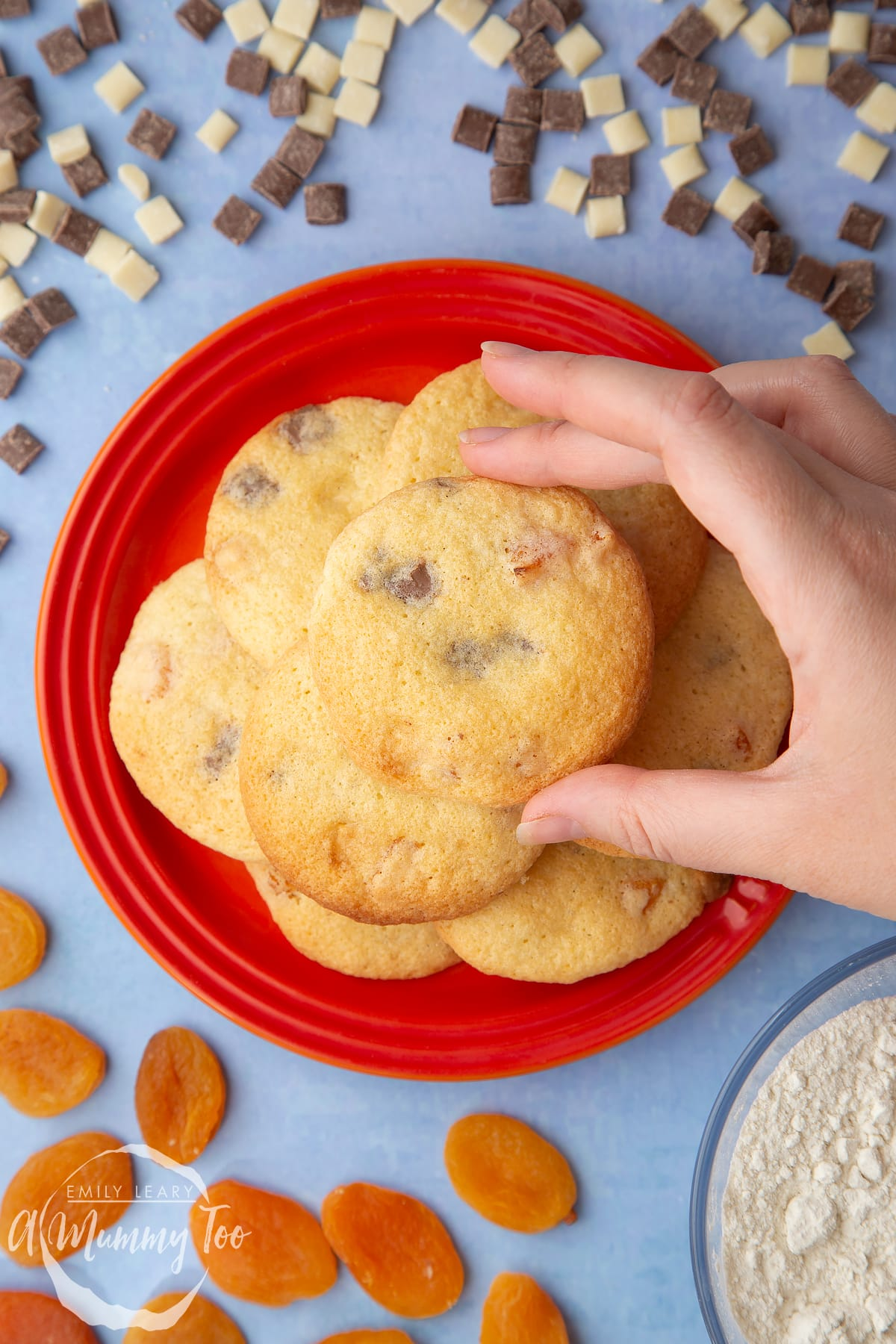Apricot chocolate chip cookies stacked on an orange plate. A hand reaches to take one.