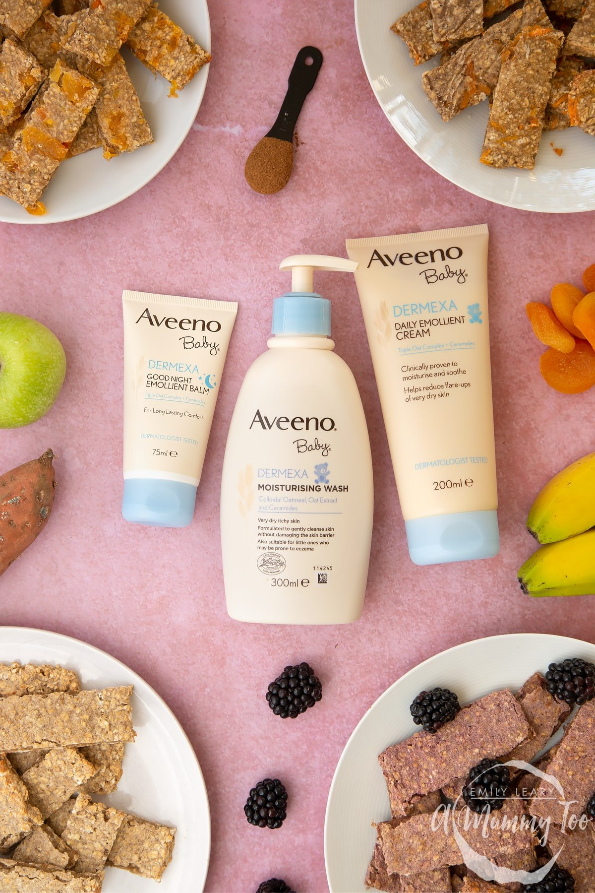 AVEENO Baby skincare products laying on a pink surface. Various flavours of oat fingers sit on plates around the edge of the frame.
