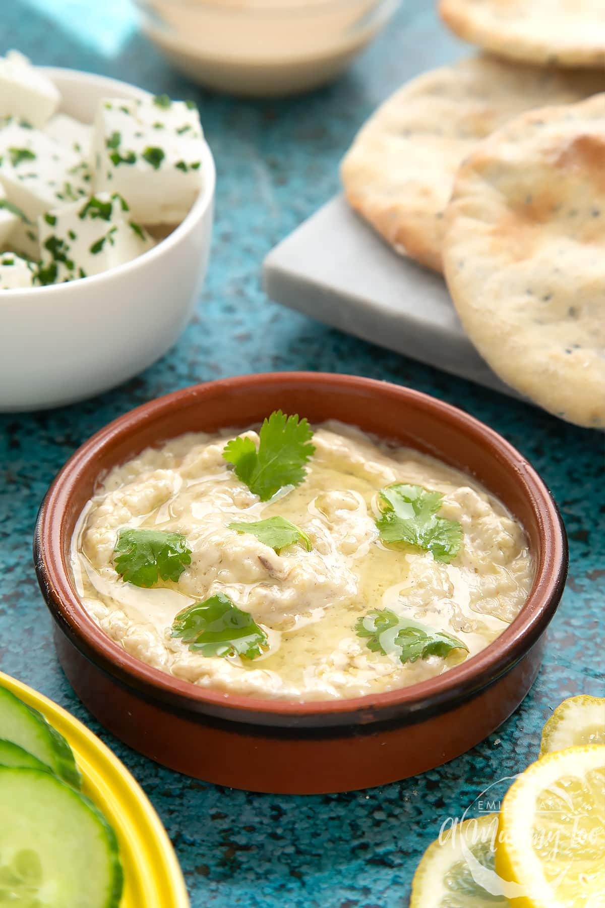 Baba ganoush in a shallow terracotta dish. Feta, cucumbers, lemon and flat bread surround the dish.