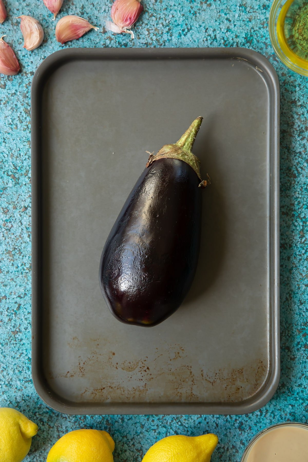 An aubergine on a baking tray. Ingredients to make an easy baba ganoush recipe surround the tray.