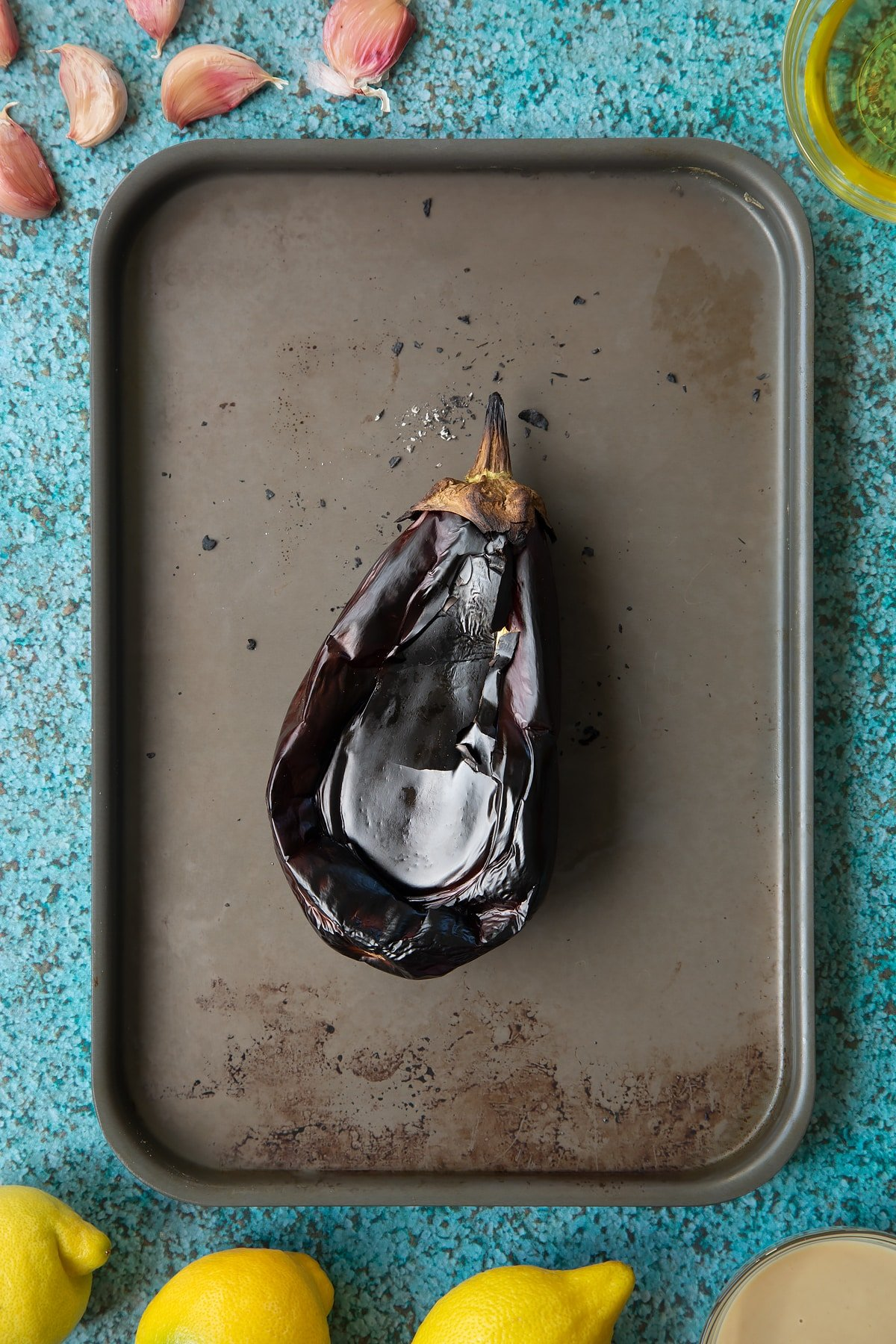 A charred aubergine on a baking tray. Ingredients to make an easy baba ganoush recipe surround the tray.