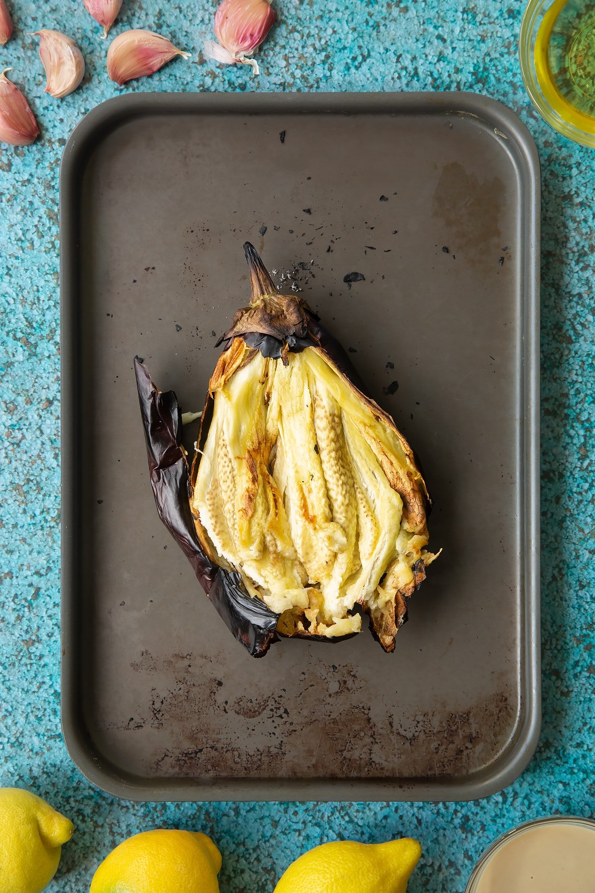 A charred aubergine on a baking tray. It has been torn open to reveal the flesh inside. Ingredients to make an easy baba ganoush recipe surround the tray.