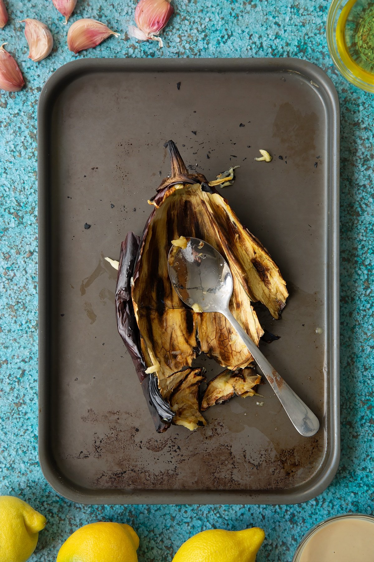 A charred aubergine skin on a baking tray with a spoon. Ingredients to make an easy baba ganoush recipe surround the tray.