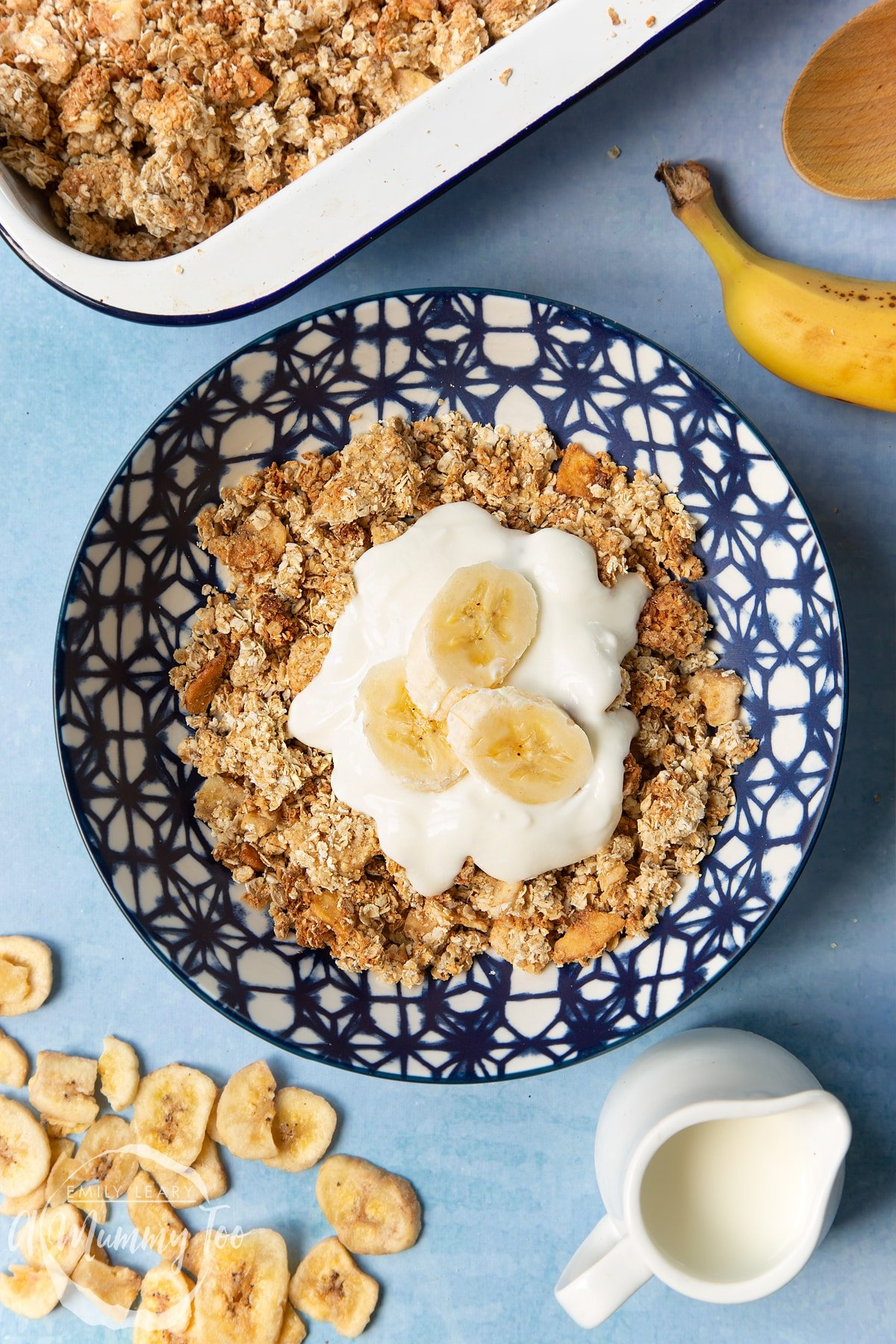 Banana coconut granola in a bowl, topped with yogurt and fresh banana slices. Ingredients surround the bowl.