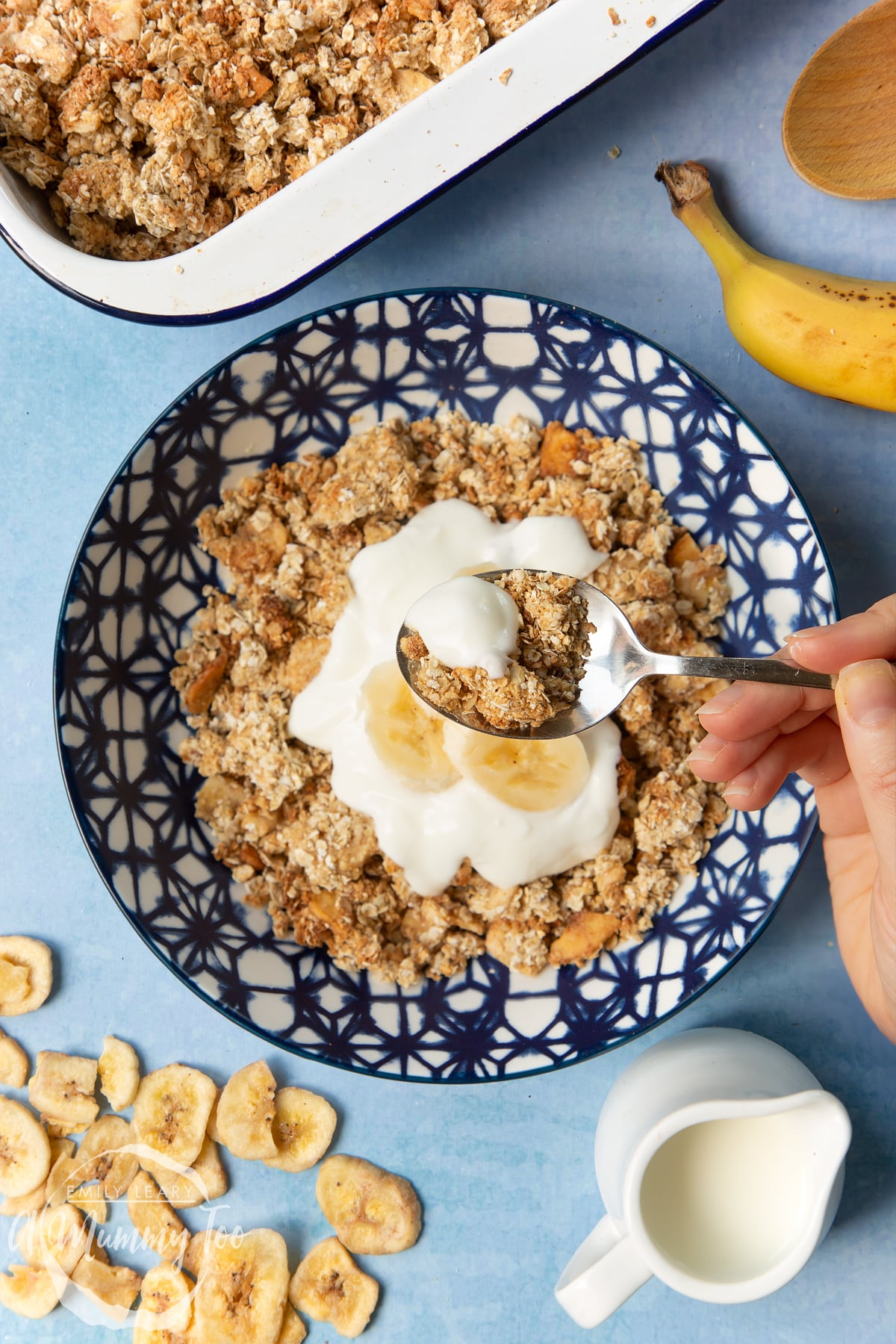 Banana coconut granola served in a blue and white bowl, topped with yogurt and banana. A spoon lifts granola from the bowl.