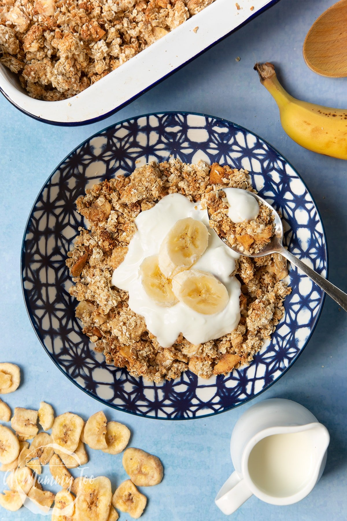 Banana coconut granola served in a blue and white bowl, topped with yogurt and banana. A spoon rests in the bowl.