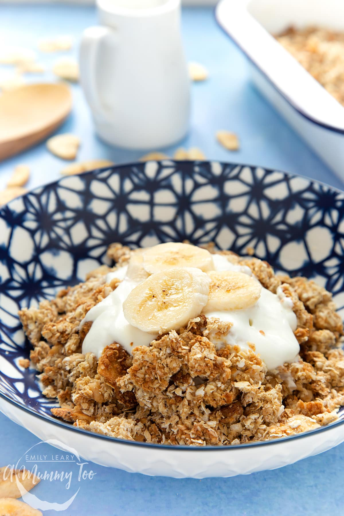 Banana coconut granola served in a blue and white bowl, topped with yogurt and banana. A jug of milk is shown in the background.