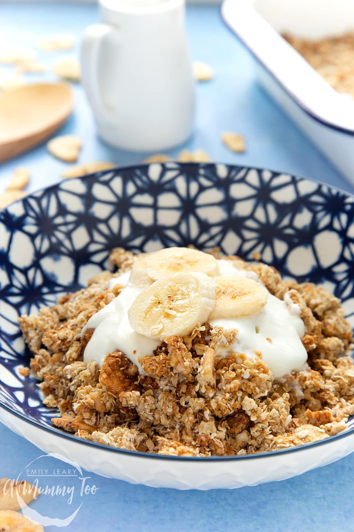 Banana coconut granola in a bowl, topped with yogurt and fresh banana slices.