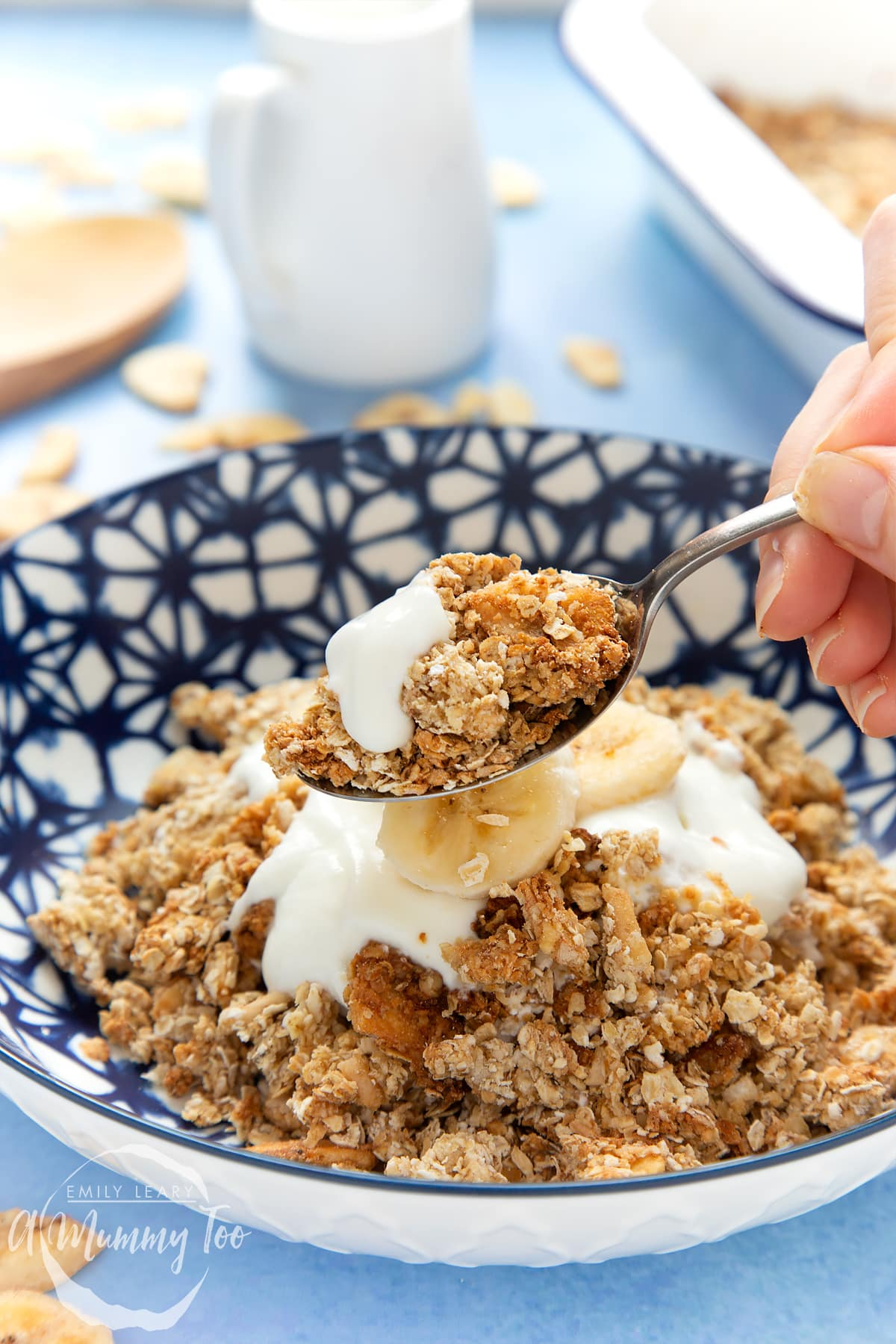 Banana coconut granola in a bowl, topped with yogurt and fresh banana slices. A hand holds a spoon filled with granola.