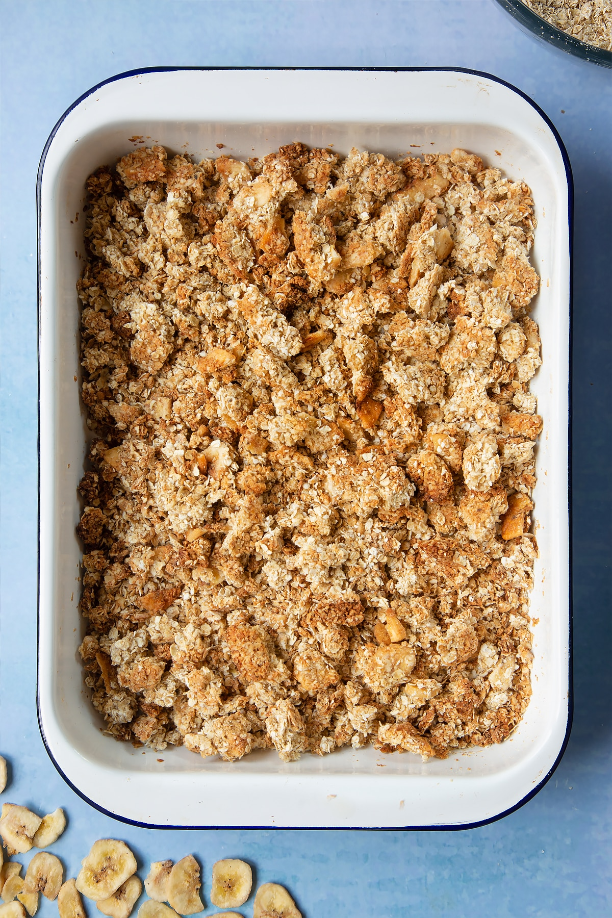 A white, medium-sized roasting tray filled with crumbled banana coconut granola.