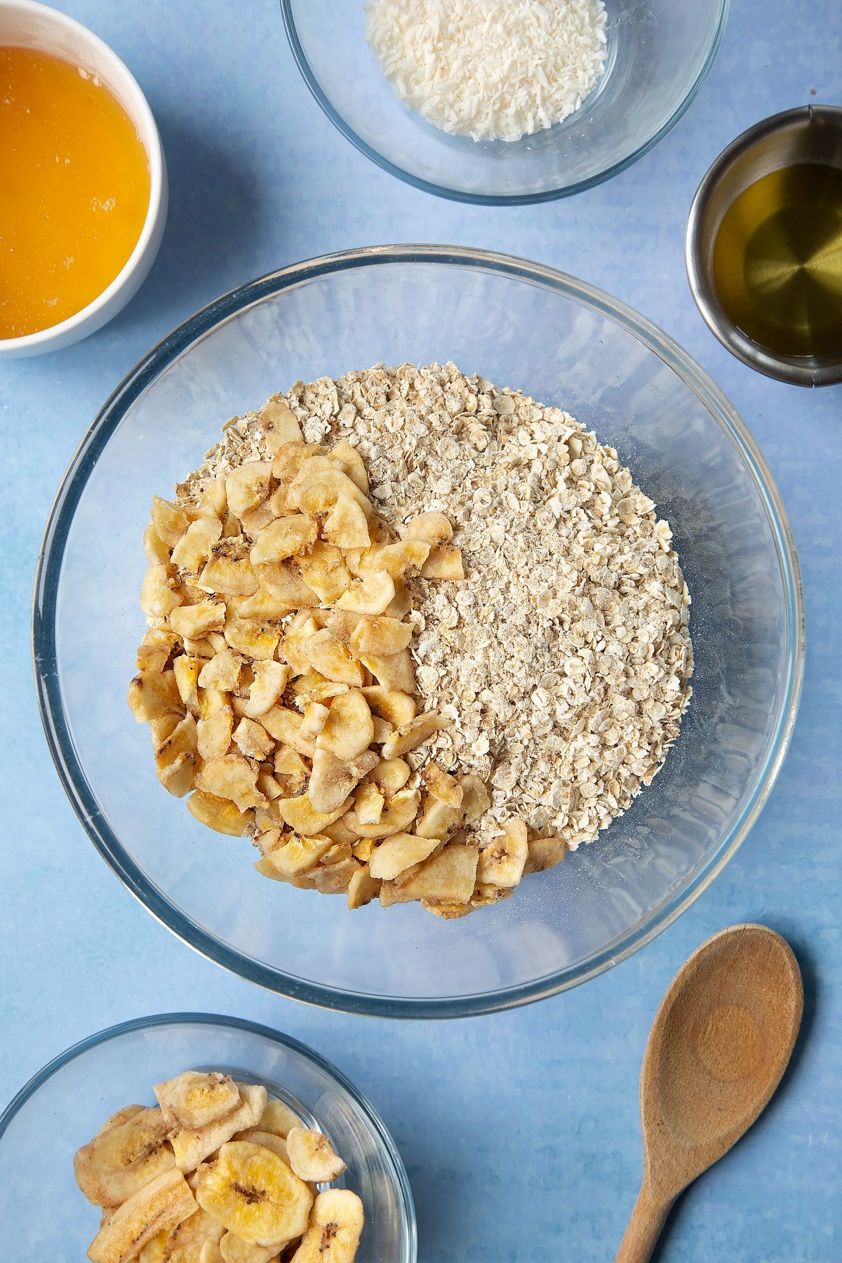 A large glass mixing bowl containing rolled oats and dried banana chips. Ingredients to make a banana coconut granola recipe surround the bowl.