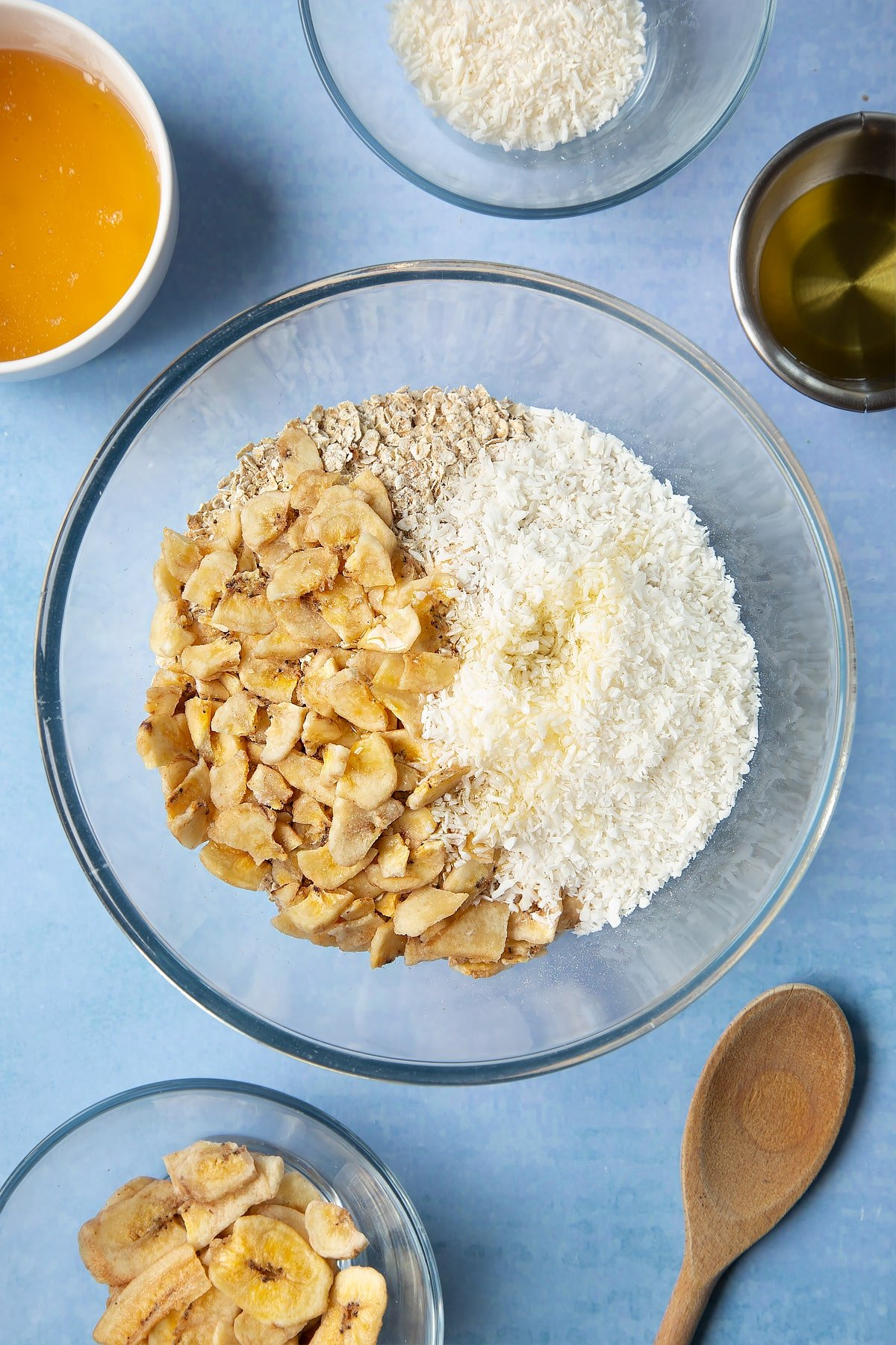A large glass mixing bowl containing rolled oats, dried banana chips, desiccated coconut and oil. Ingredients to make a banana coconut granola recipe surround the bowl.