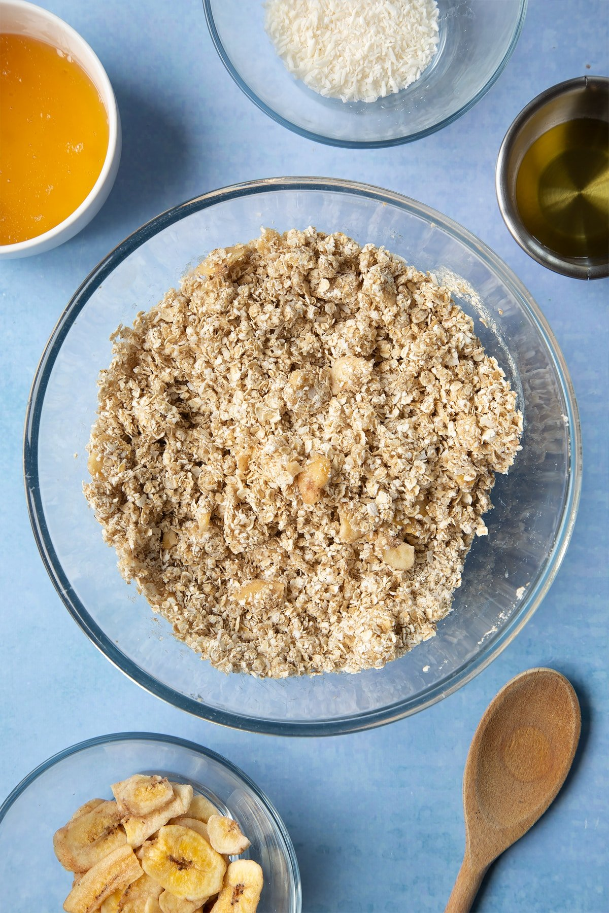 A large glass mixing bowl containing rolled oats, dried banana chips, desiccated coconut, oil and honey mixed together. Ingredients to make a banana coconut granola recipe surround the bowl.