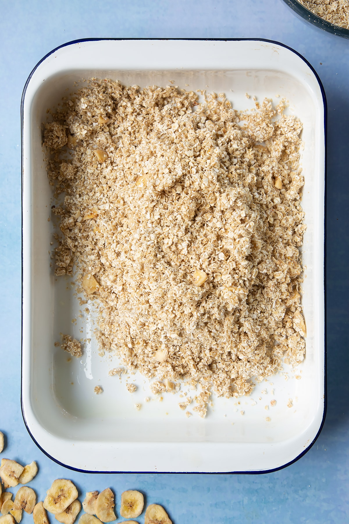 A white, medium-sized roasting tray with banana coconut granola mix tipped into it.