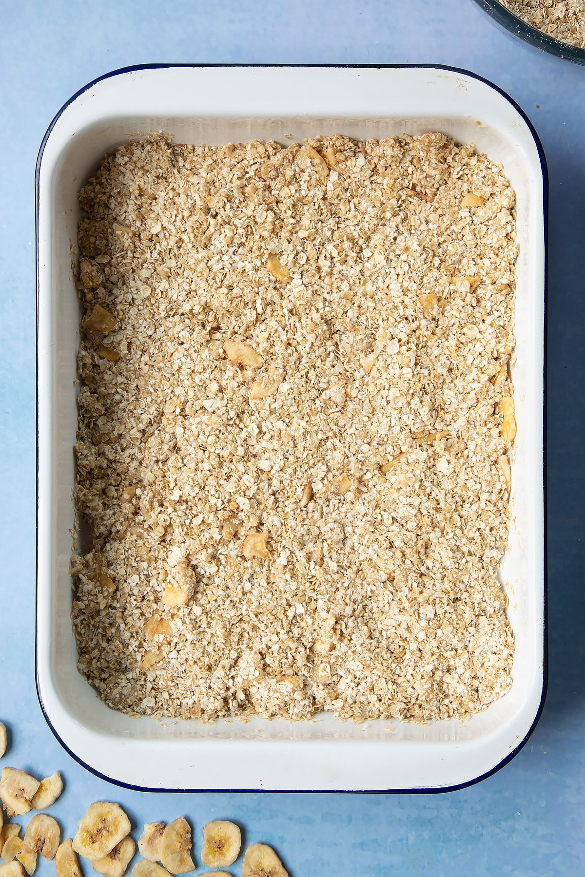 A white, medium-sized roasting tray with banana coconut granola mix pressed into it.