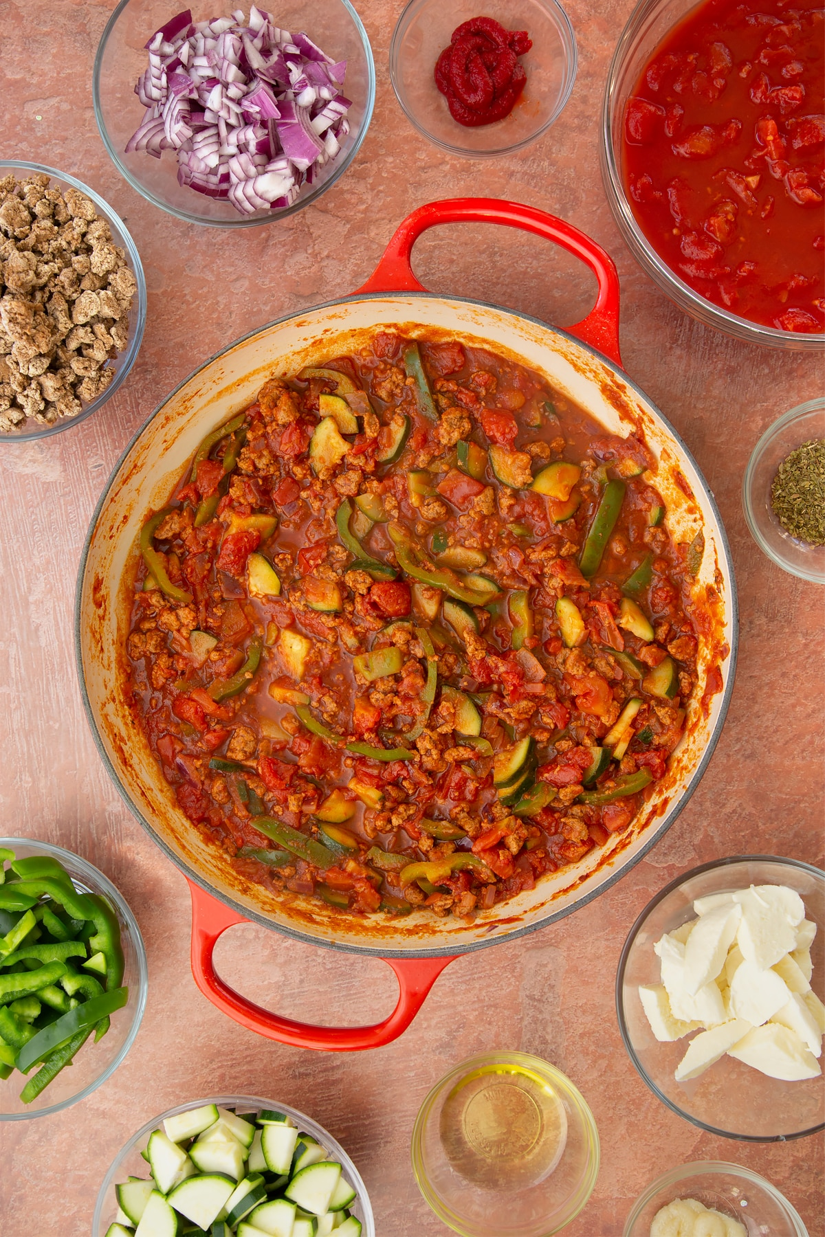 A casserole dish containing a bolognese sauce of red onion, garlic, sliced peppers, courgettes, mince, chopped tomatoes, tomato puree and dried oregano. Ingredients to make bolognese al forno surround the dish.