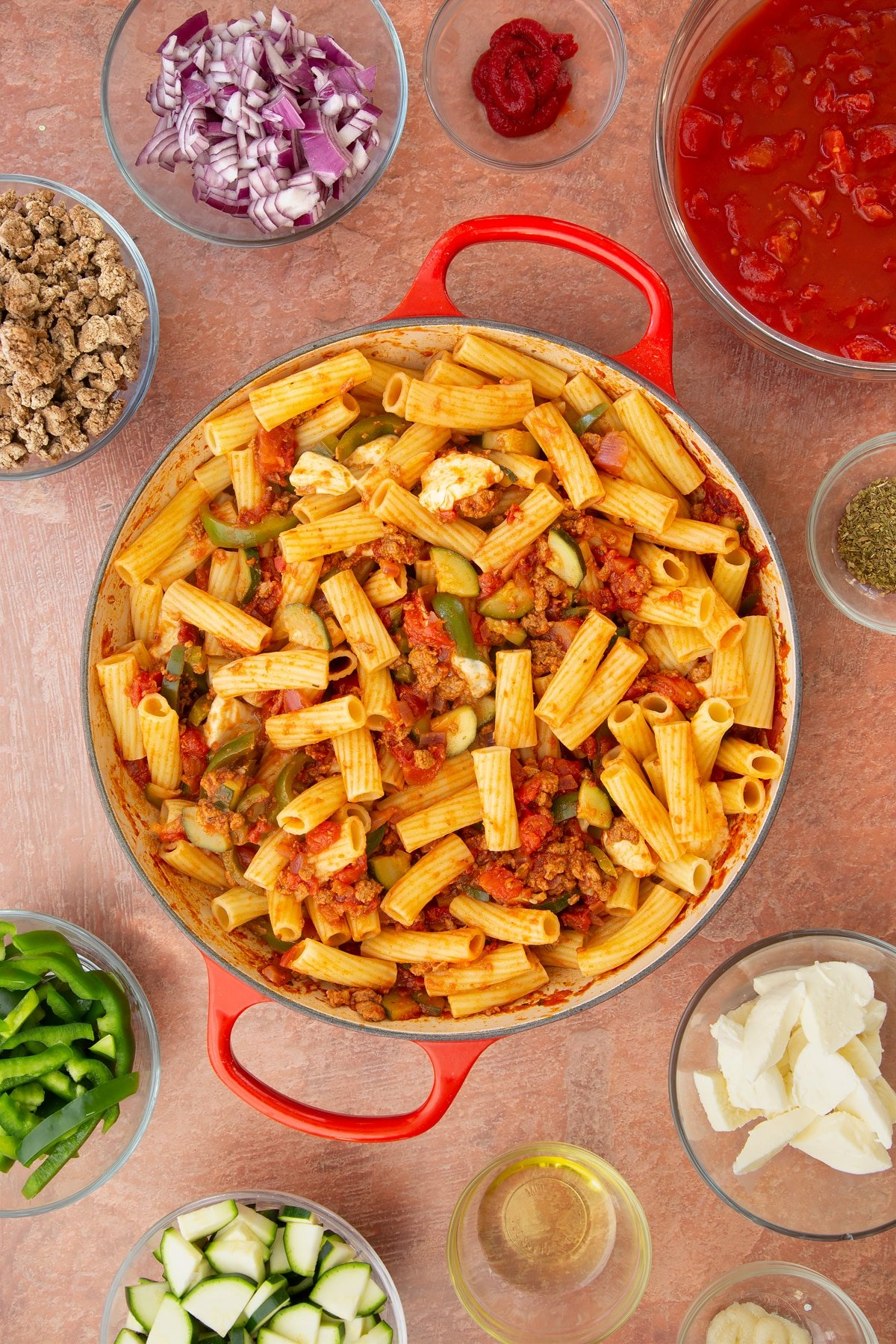 A casserole dish containing a bolognese sauce mixed with cooked pasta and torn mozzarella. Ingredients to make bolognese al forno surround the dish.