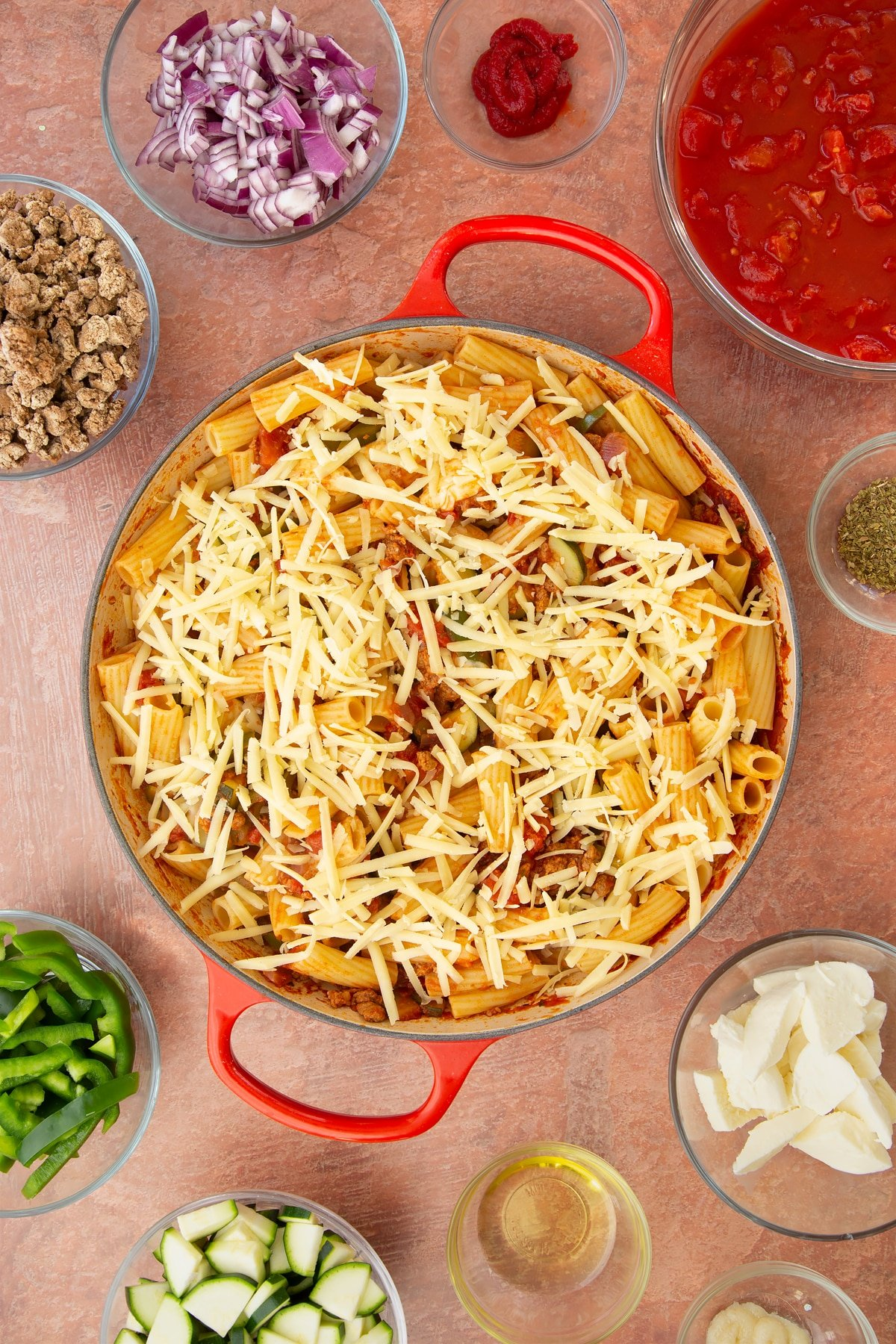 A casserole dish containing a bolognese sauce mixed with cooked pasta and torn mozzarella, topped with grated cheese. Ingredients to make bolognese al forno surround the dish.