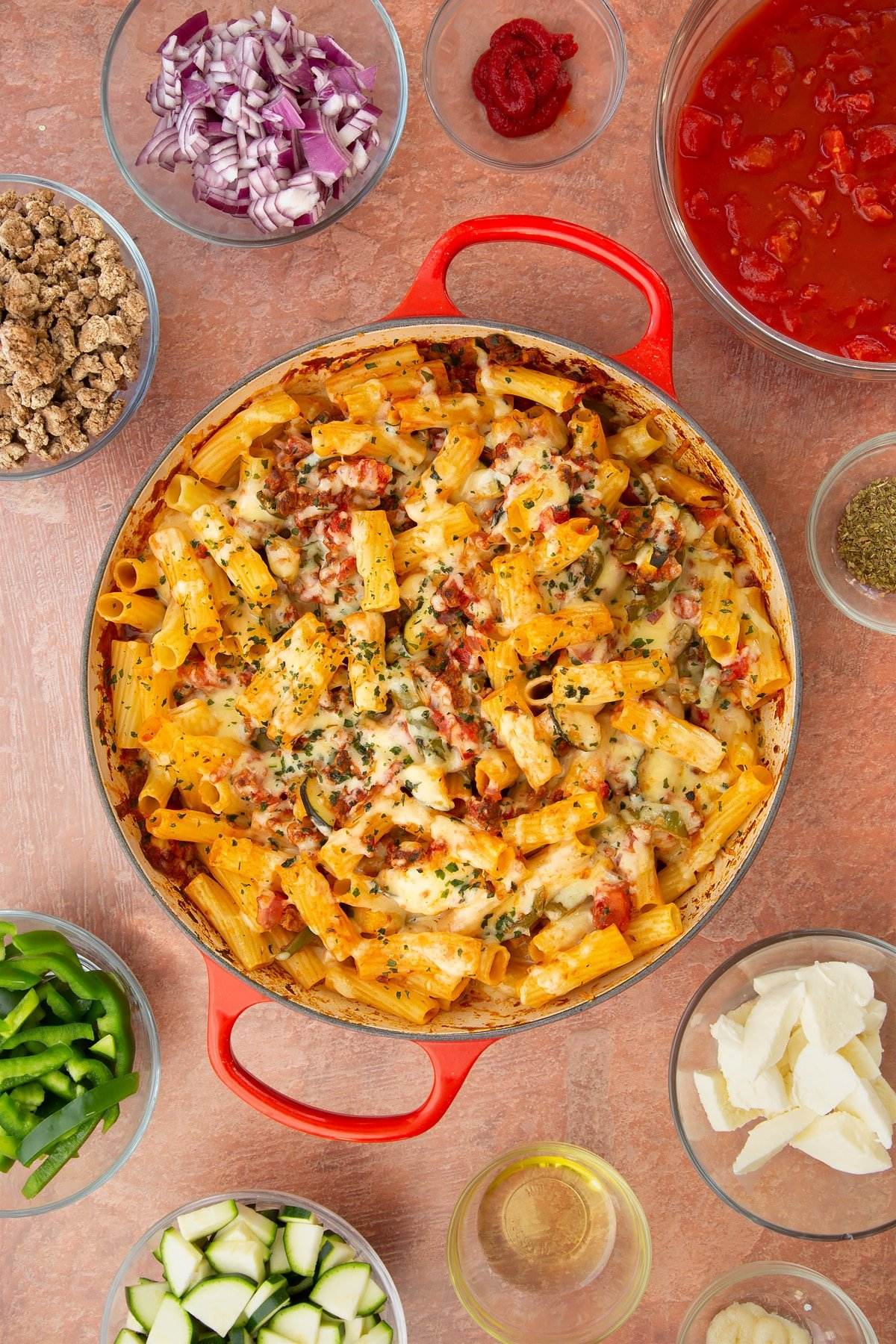 A casserole dish containing freshly baked bolognese al forno. Ingredients surround the dish.