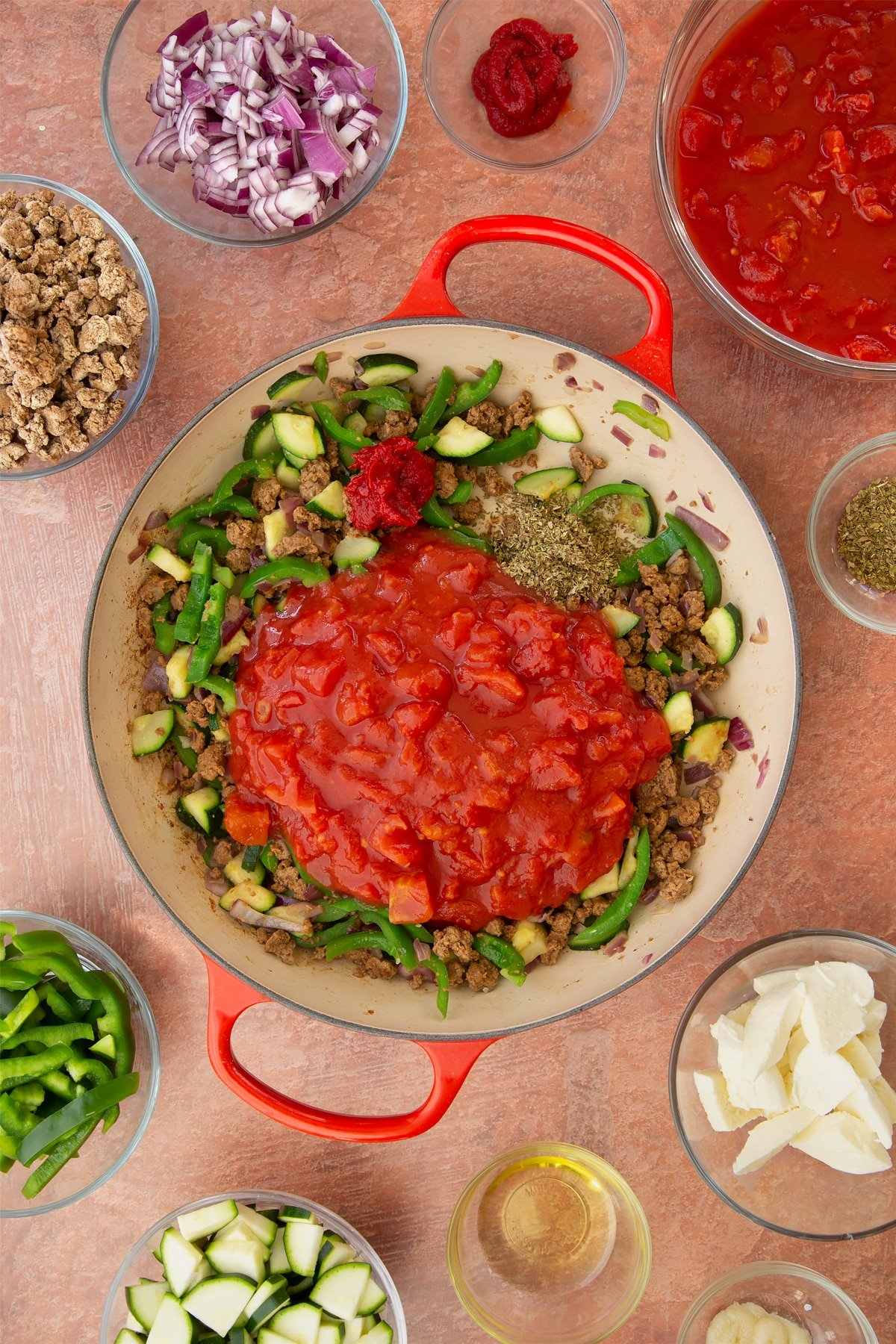 A casserole dish containing fried red onion, garlic, sliced peppers, courgettes and mince. Chopped tomatoes, tomato puree and dried oregano is added. Ingredients to make bolognese al forno surround the dish.