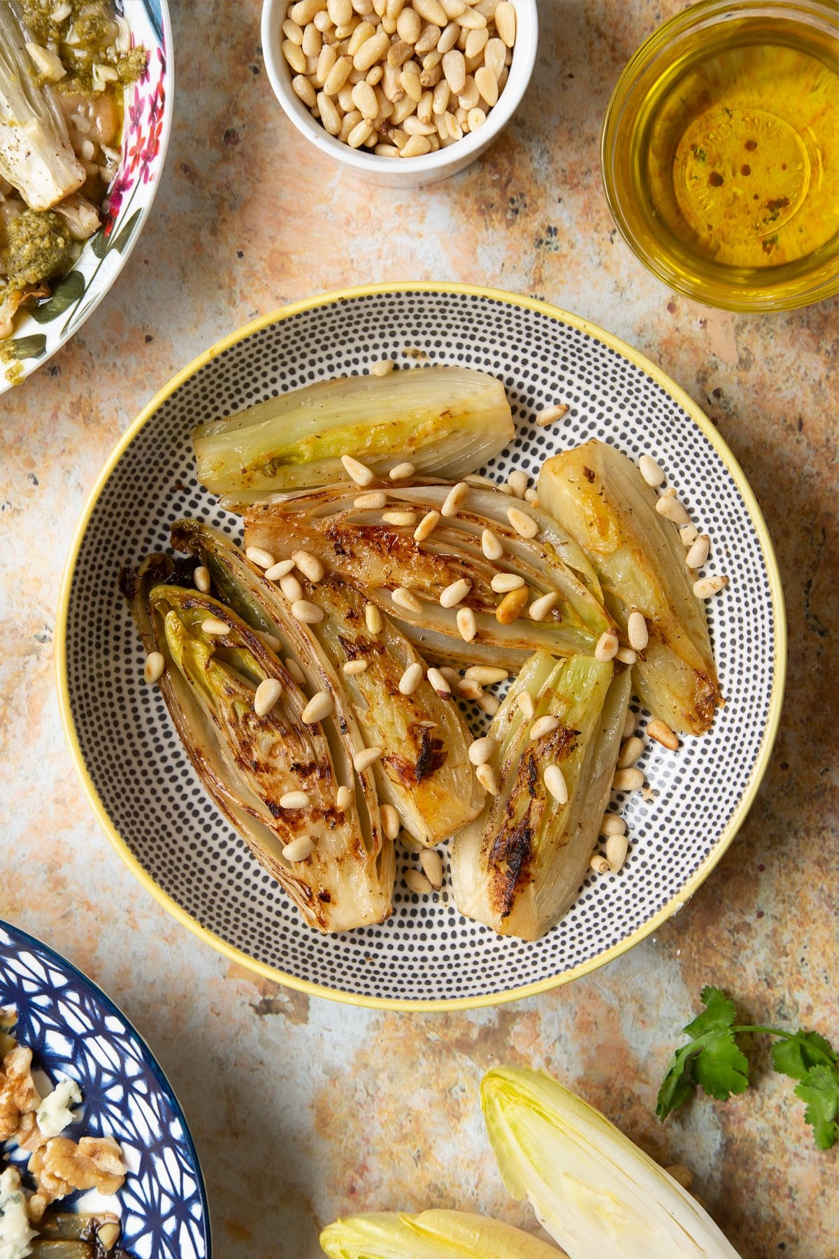 Braised chicory in a bowl with fennel and pine nuts.
