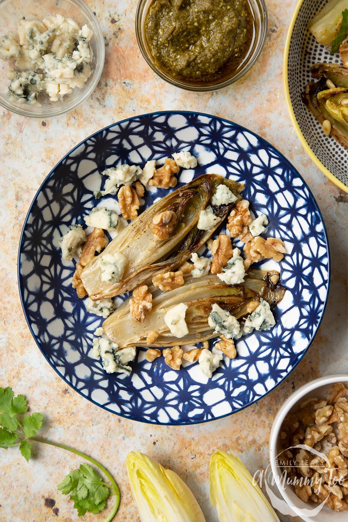 Braised chicory in a bowl with blue cheese and walnuts.