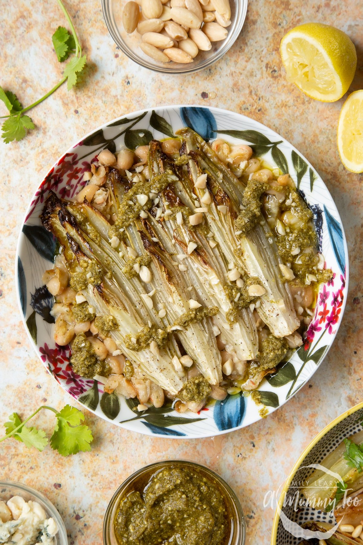 Braised chicory in a bowl with cannellini beans, pesto and chopped almonds.