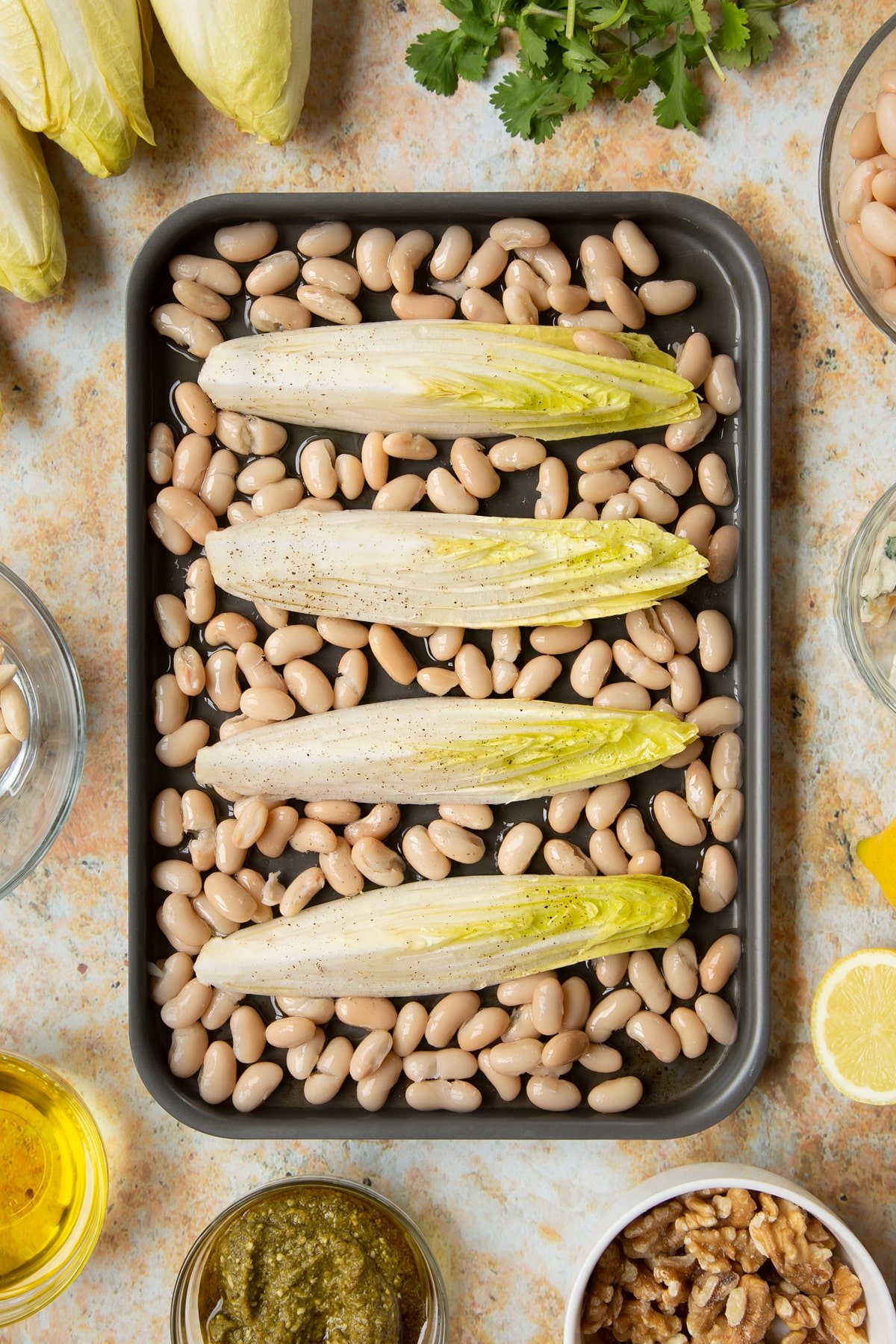 Chicory, cannellini beans and oil on a tray. They have been seasoned.