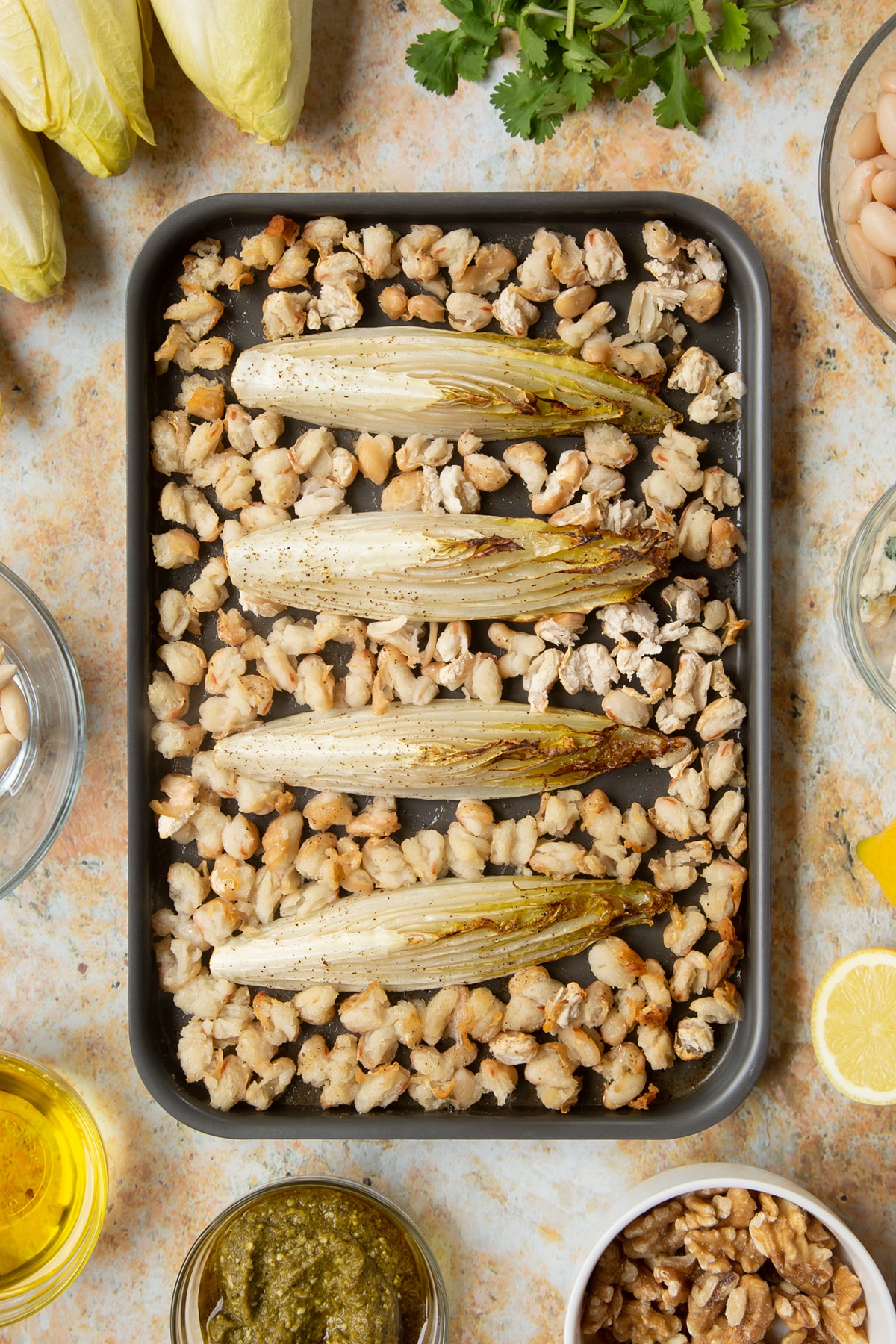 Roasted chicory and cannellini beans on a tray.