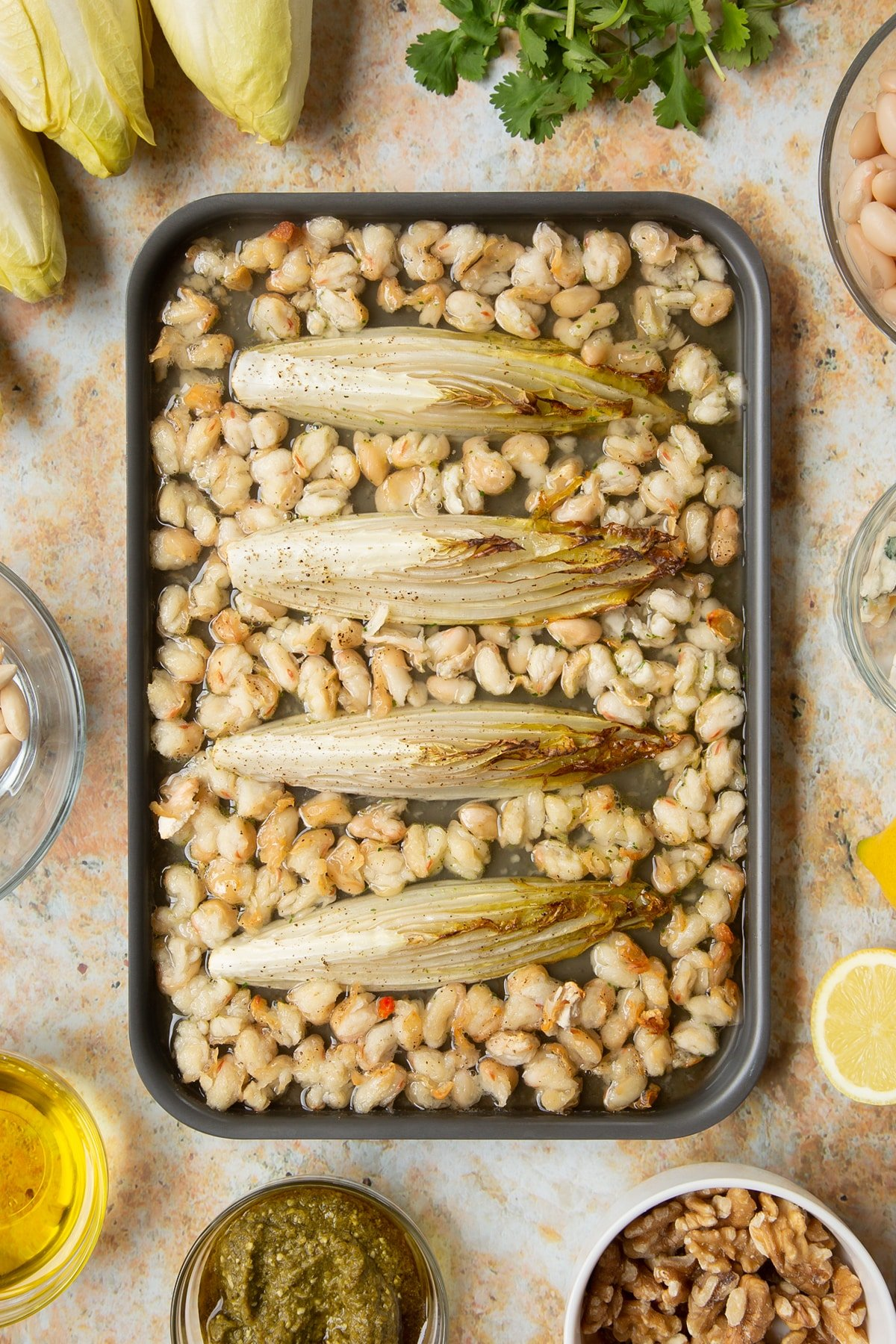 Chicory and cannellini beans braising on a tray.