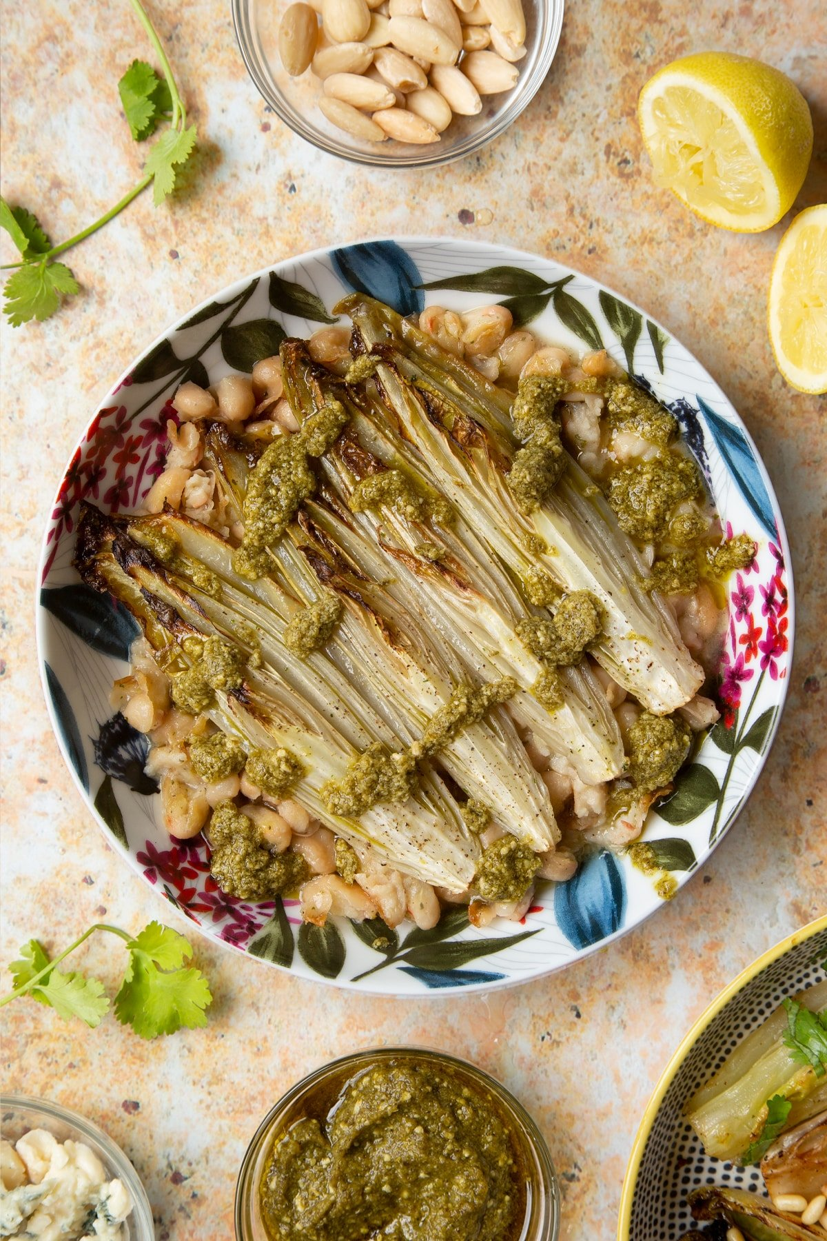 Braised chicory in a bowl with cannellini beans and pesto.