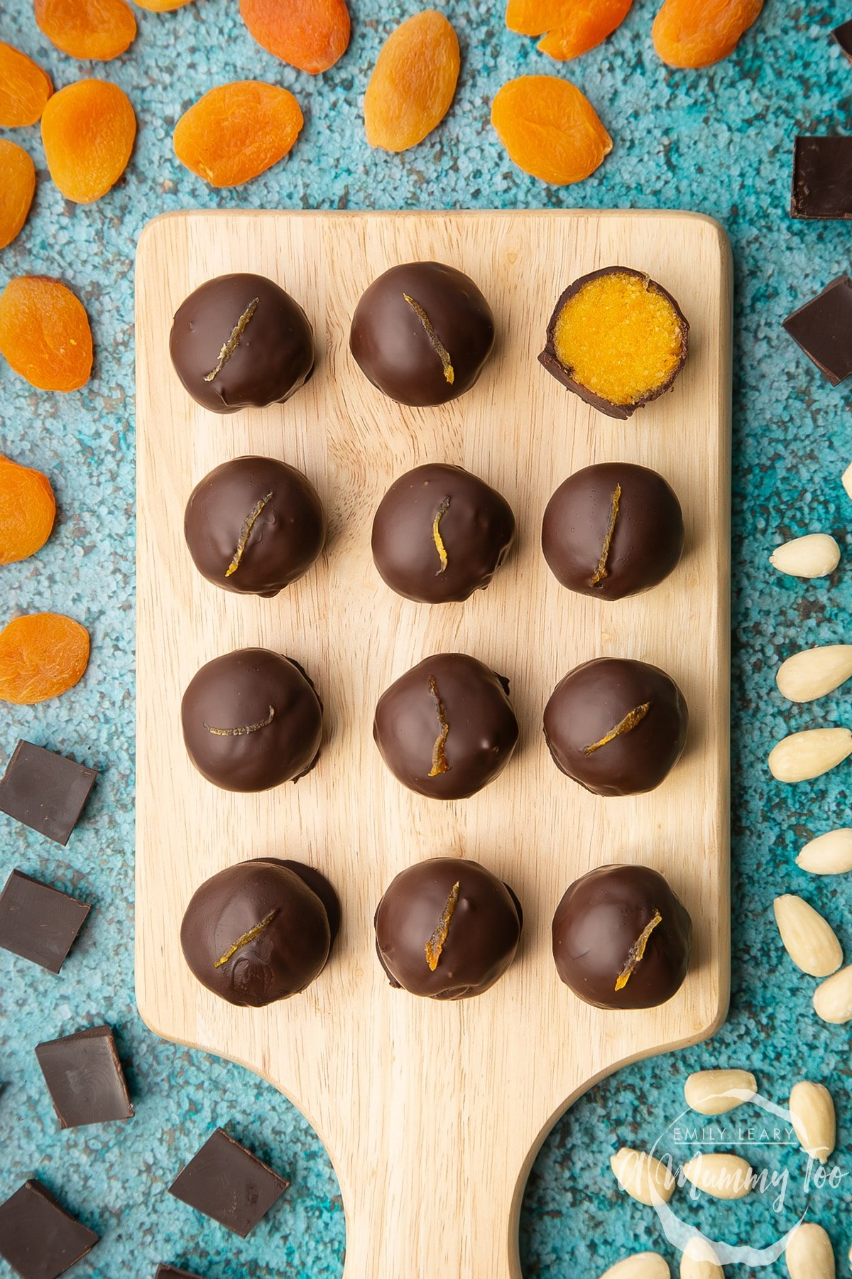 12 chocolate apricot balls arranged on a wooden board. One has been cut in half, revealing the bright orange apricot filling. Dried apricots, blanched almonds and squares of dark chocolate surround the board.