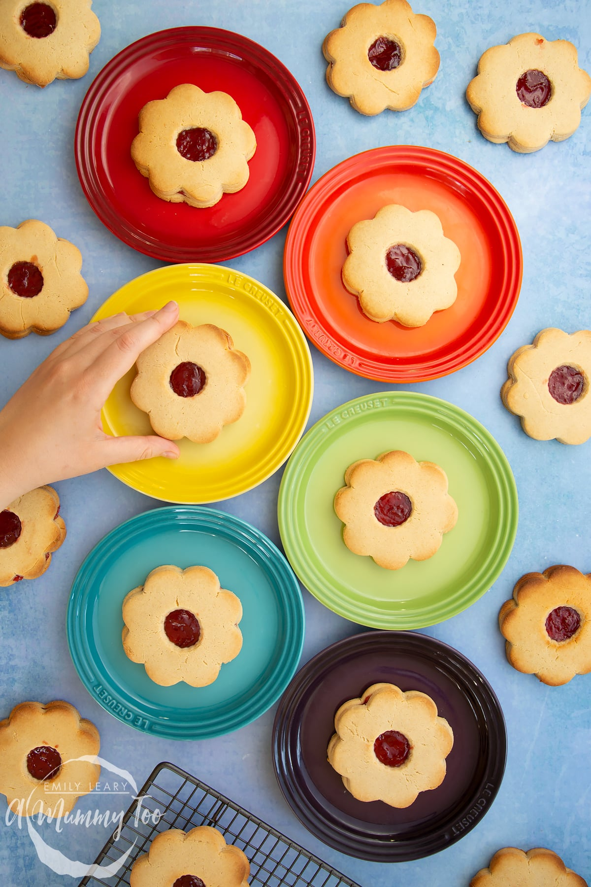 Giant jammie dodgers arranged on a variety of coloured small plates. A hand reaches in to take one from the yellow plate.
