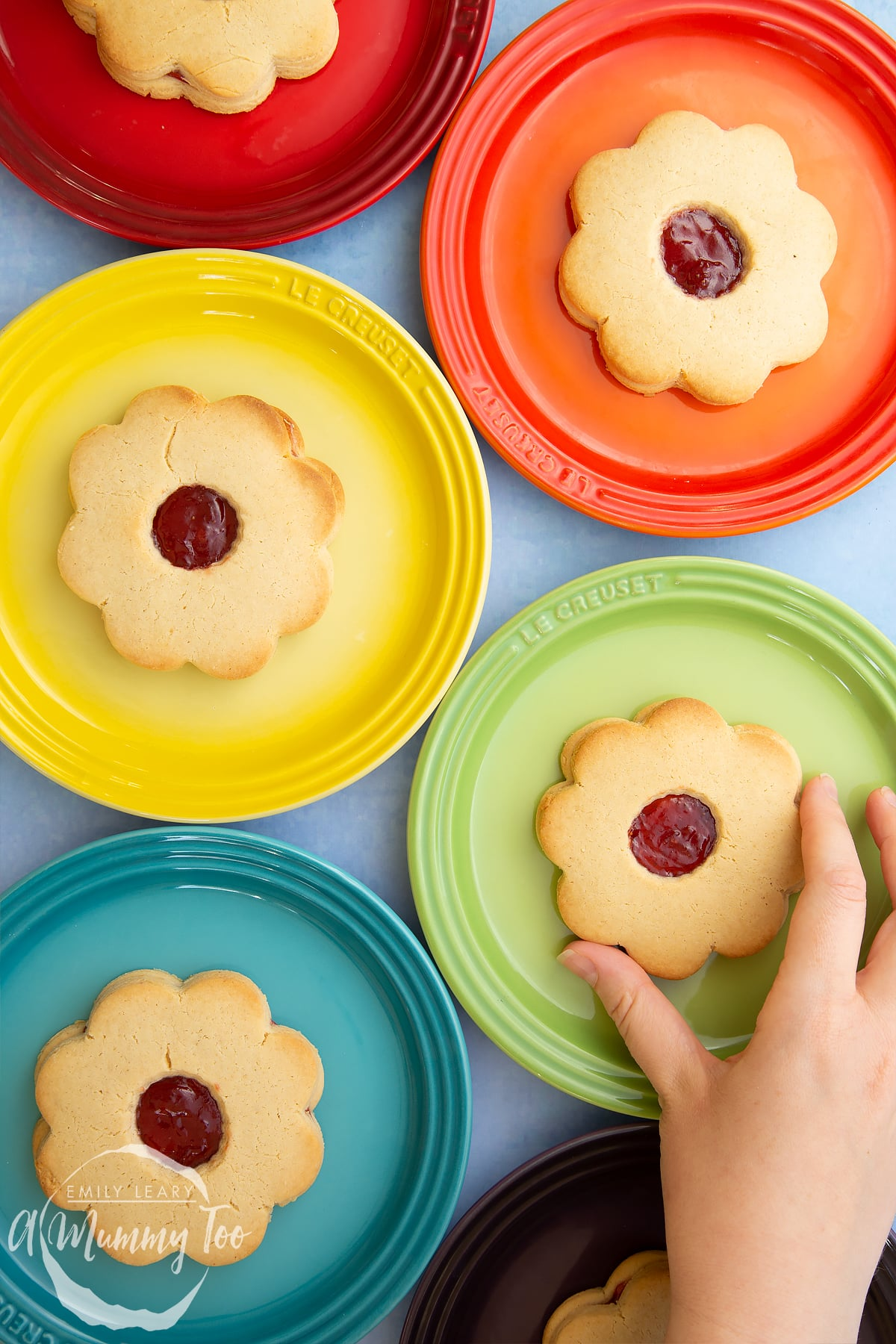 Giant jammie dodgers arranged on a variety of coloured small plates. A hand reaches in to take one from the green plate.